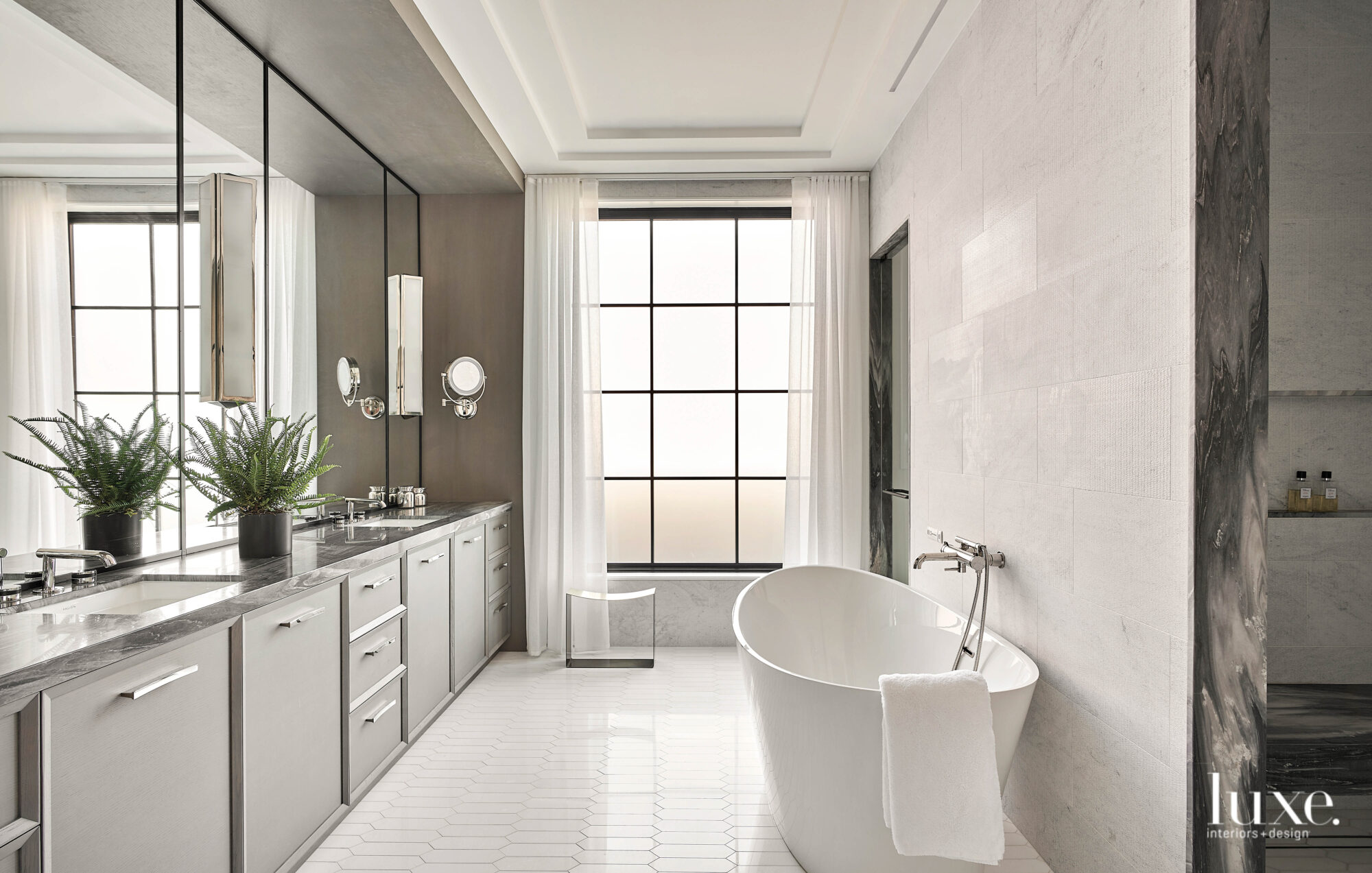 The stand-alone tub sits in front of a marble wall in the master bathroom.