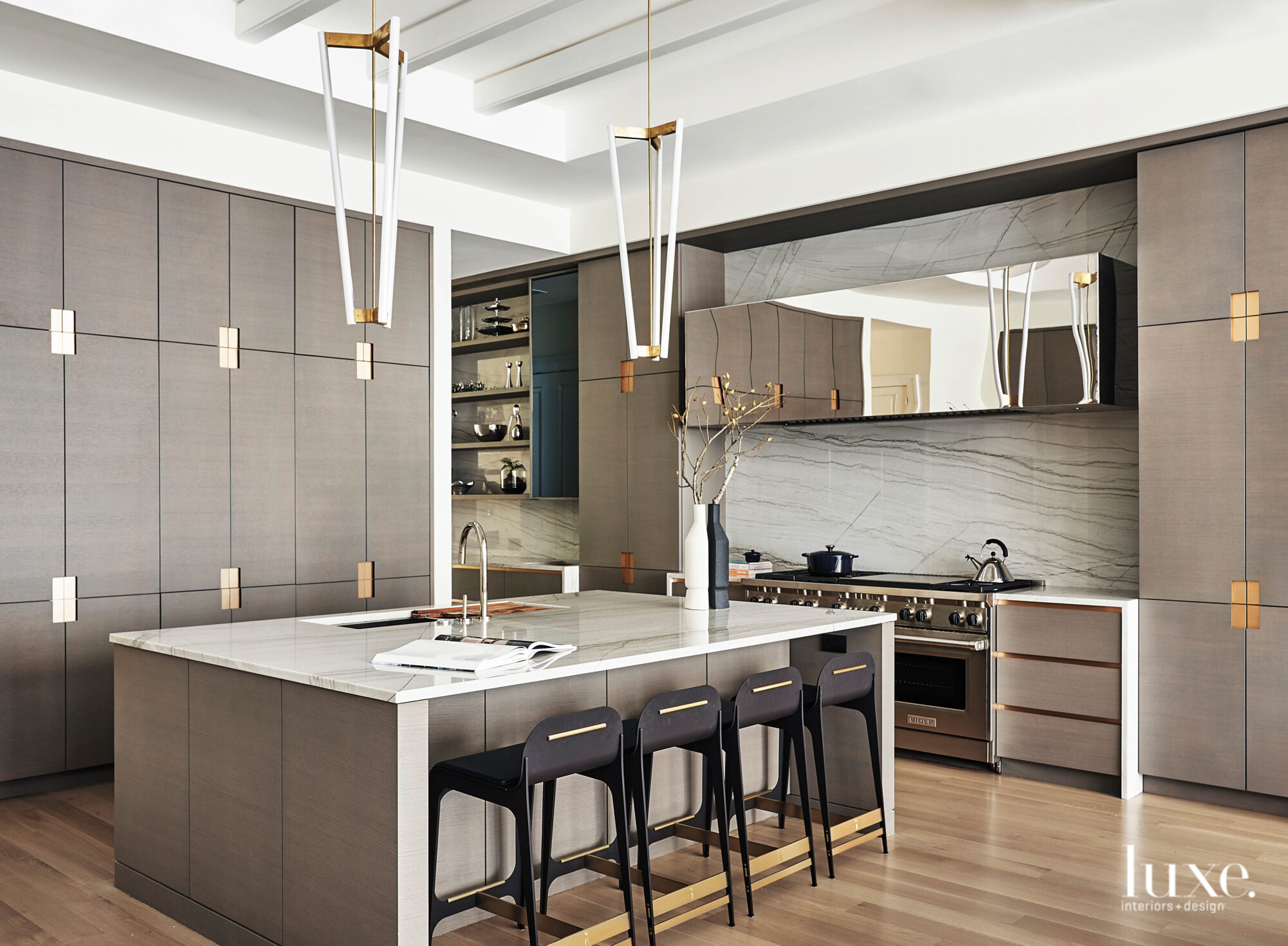 The bespoke kitchen has gray cabinetry and touches of black and brass throughout.