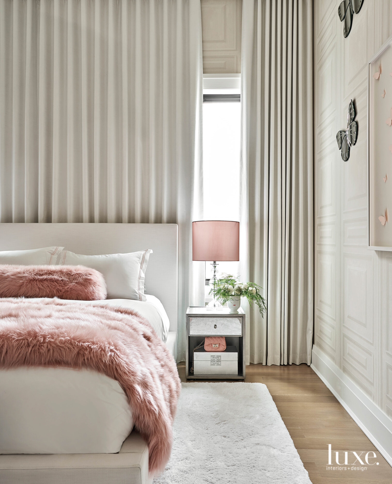 A pink throw and bedside...