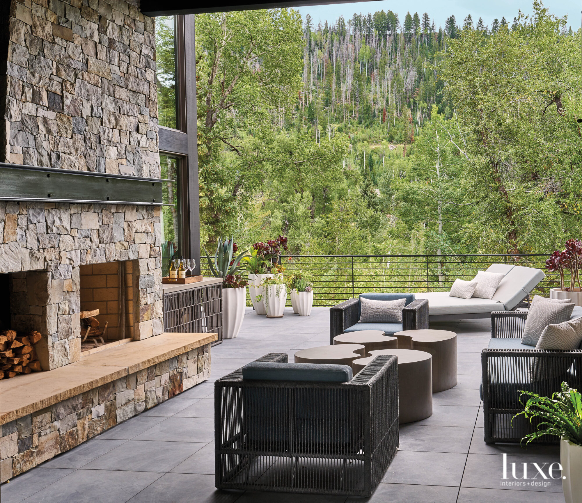 On a patio, outdoor furniture cozies up the the fireplace.