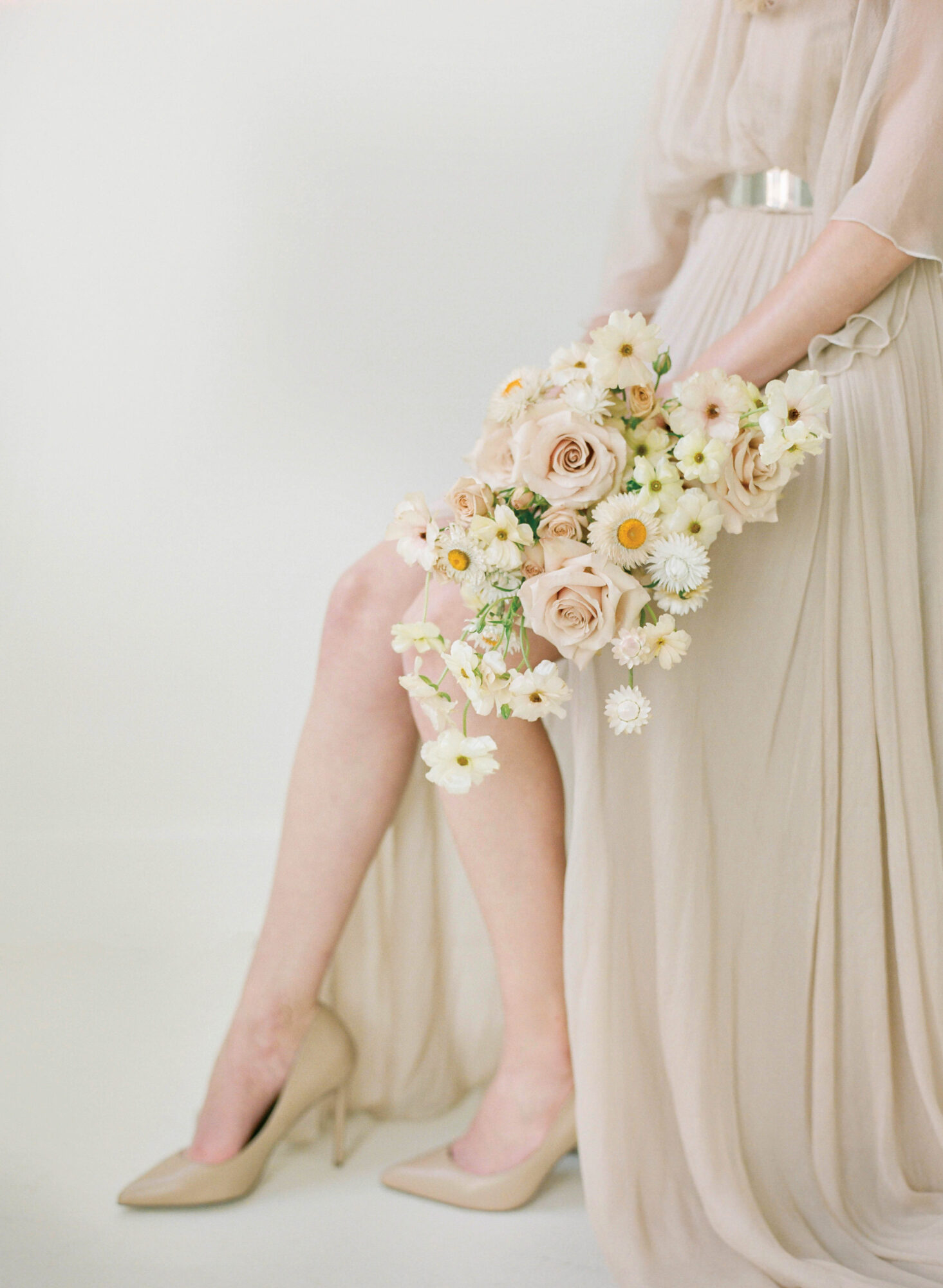 woman in ivory dress holding bouquet of flowers