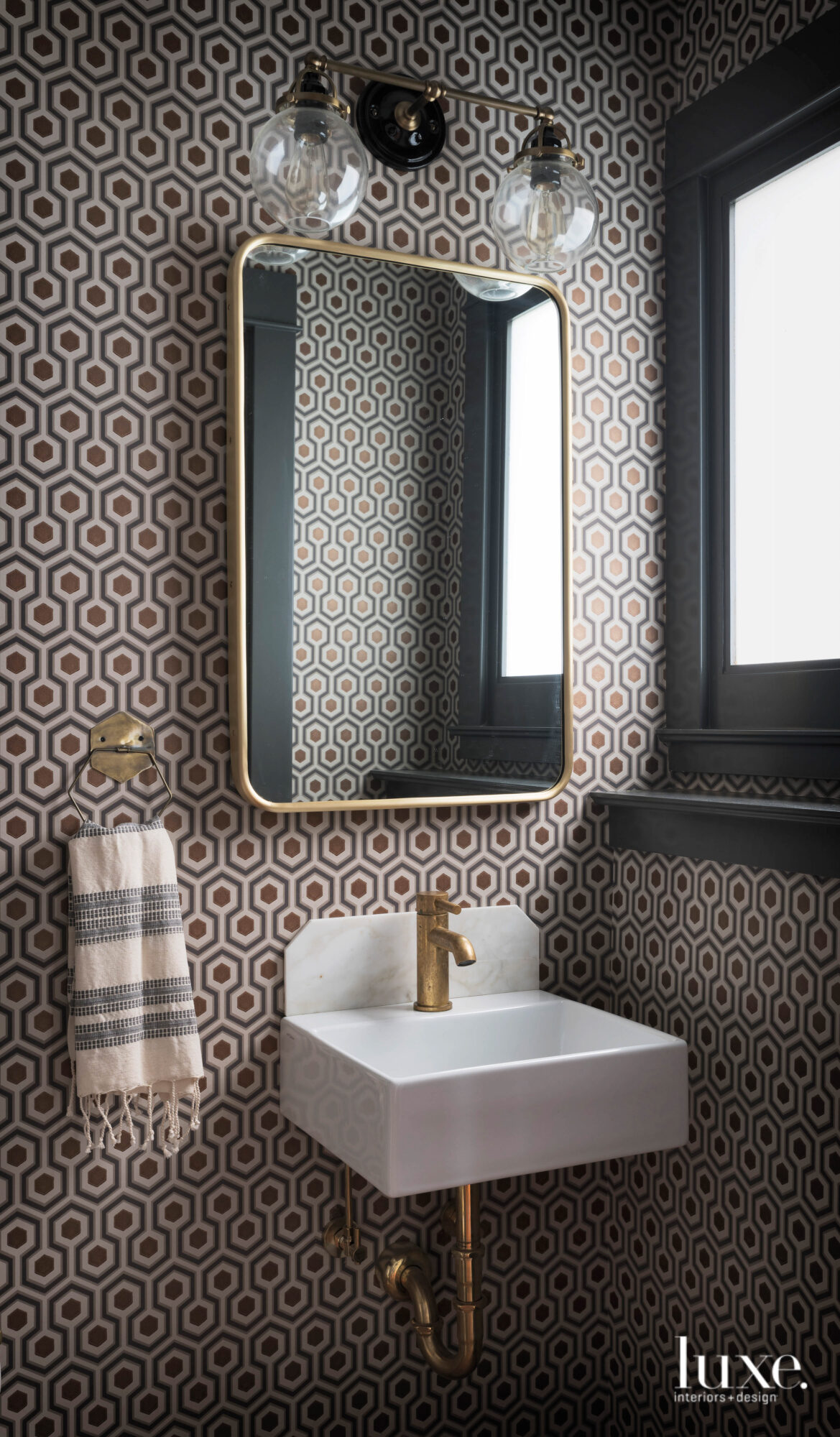 Powder room with wallpaper in...