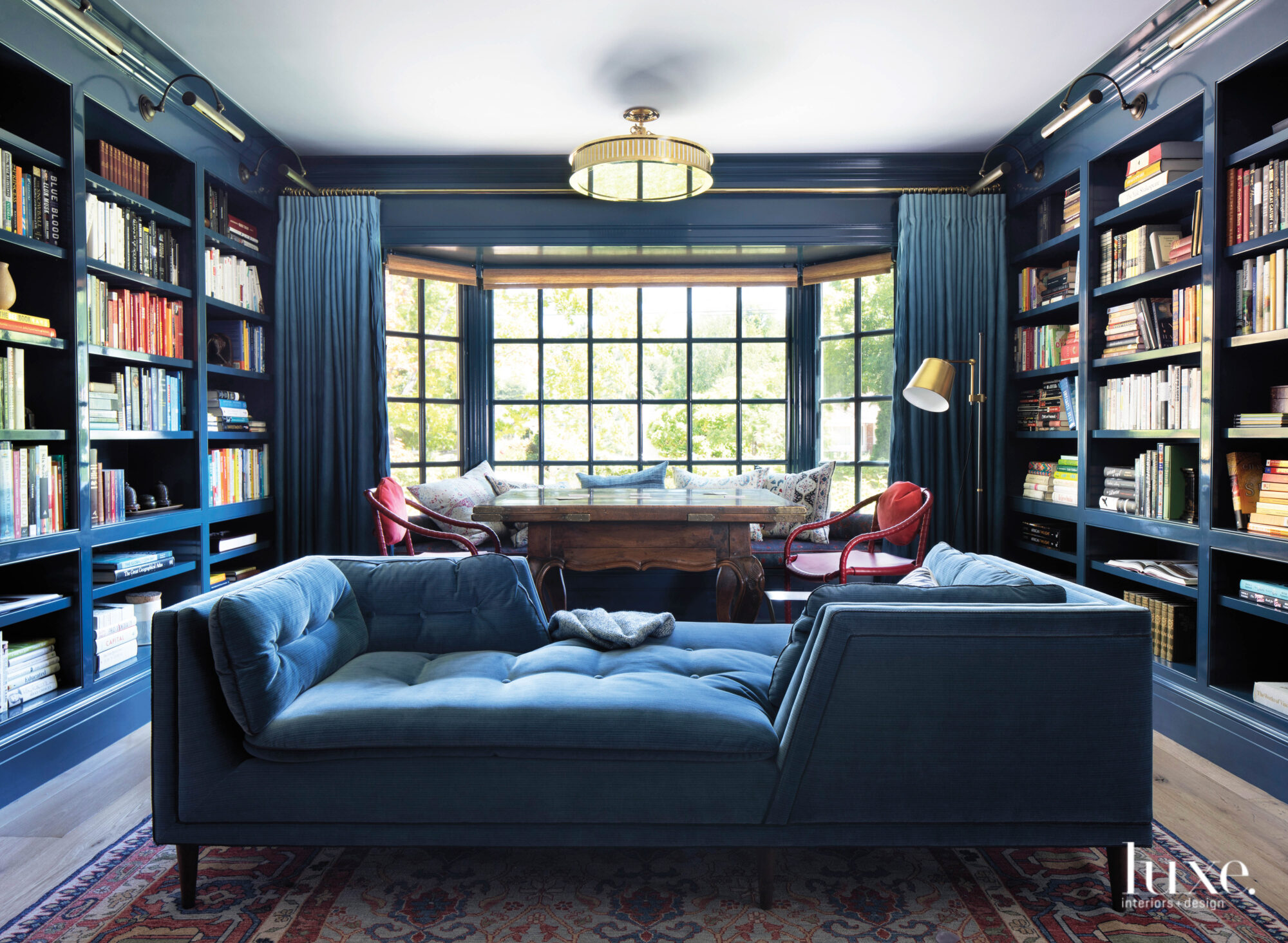 In the library, a two-sided sofa and a game table make the dark blue room multifunctional.