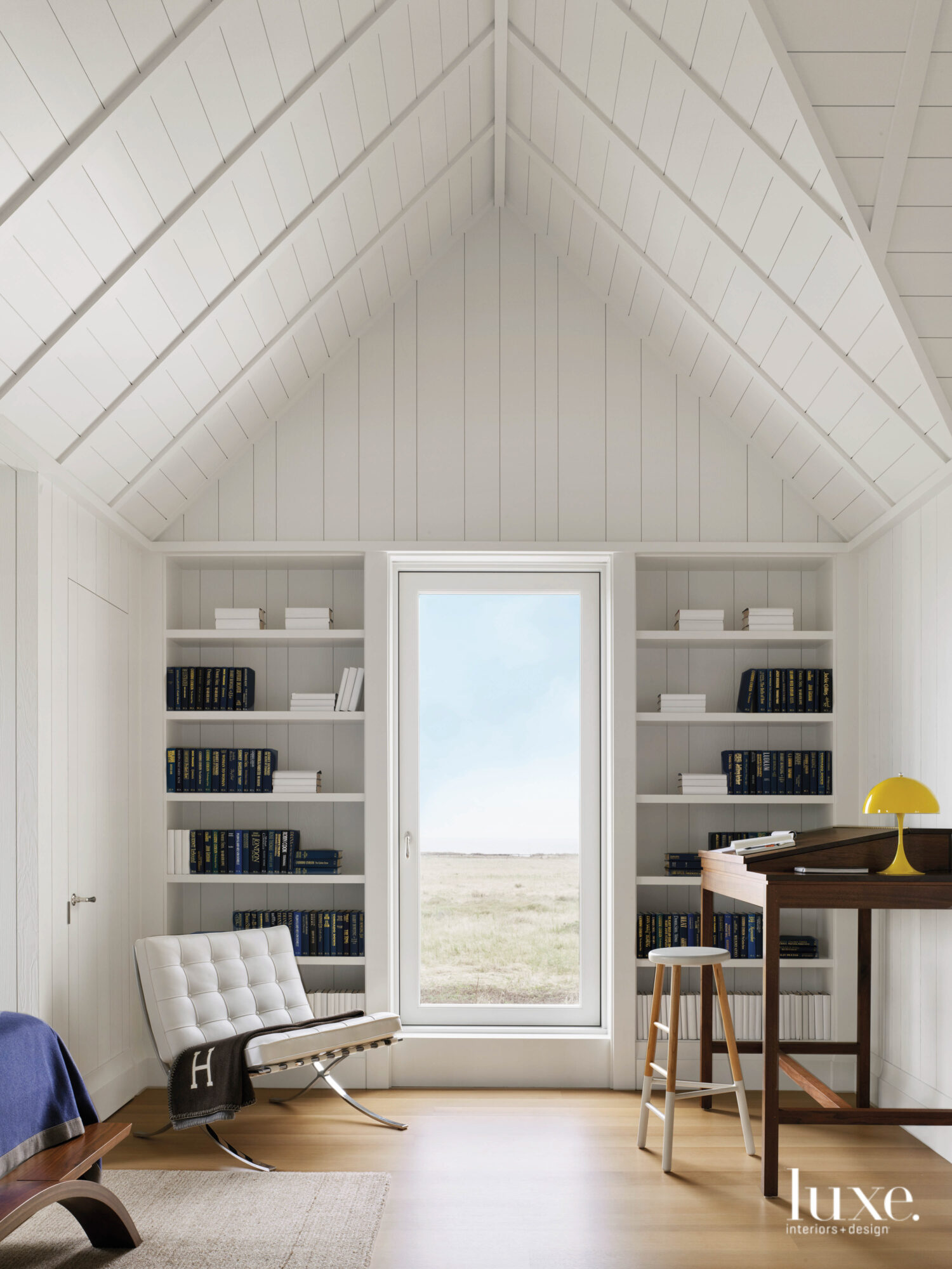 One end of the boy's room has a petite desk, white shelves and an ocean view.