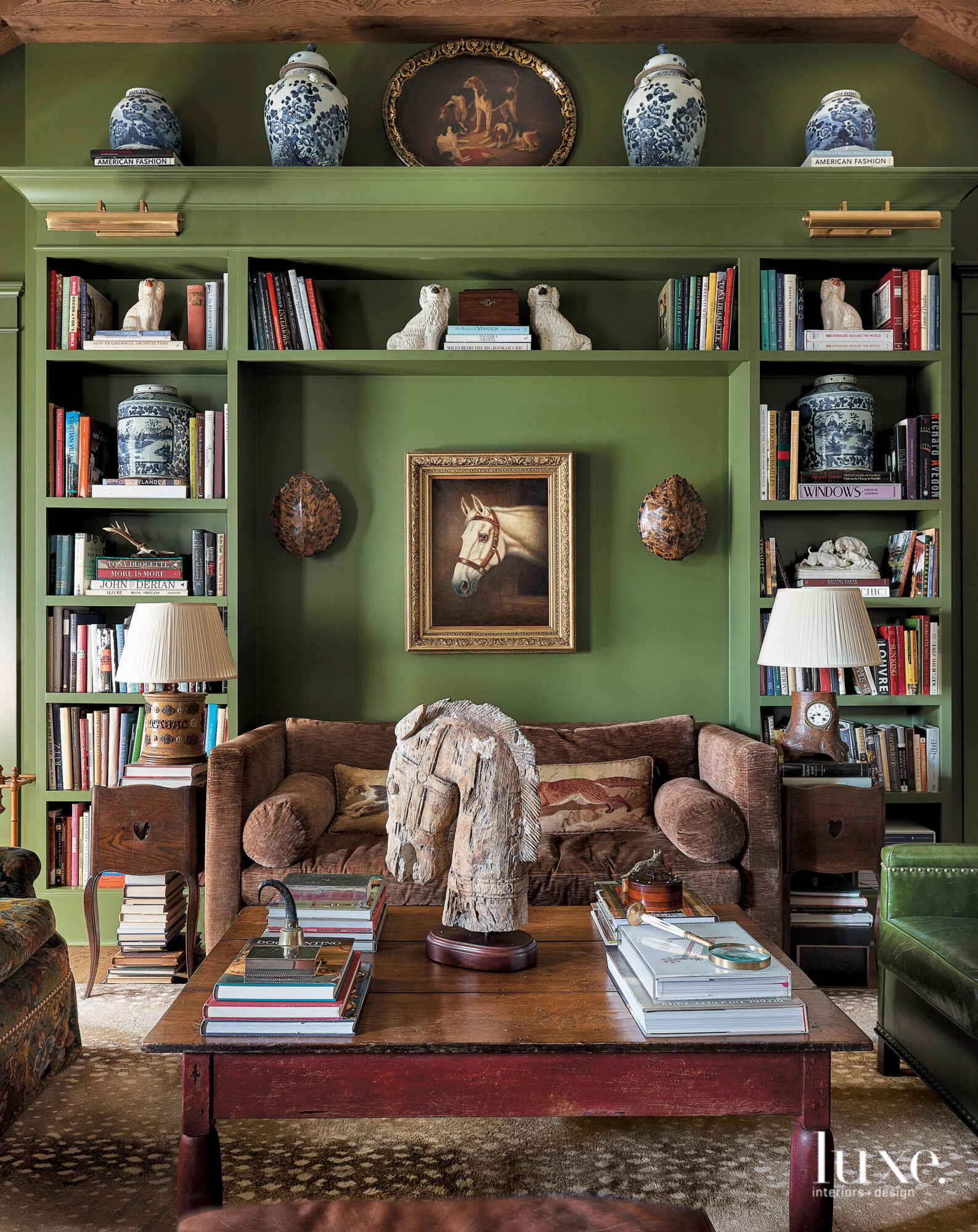 Room with green walls, bookshelves,...