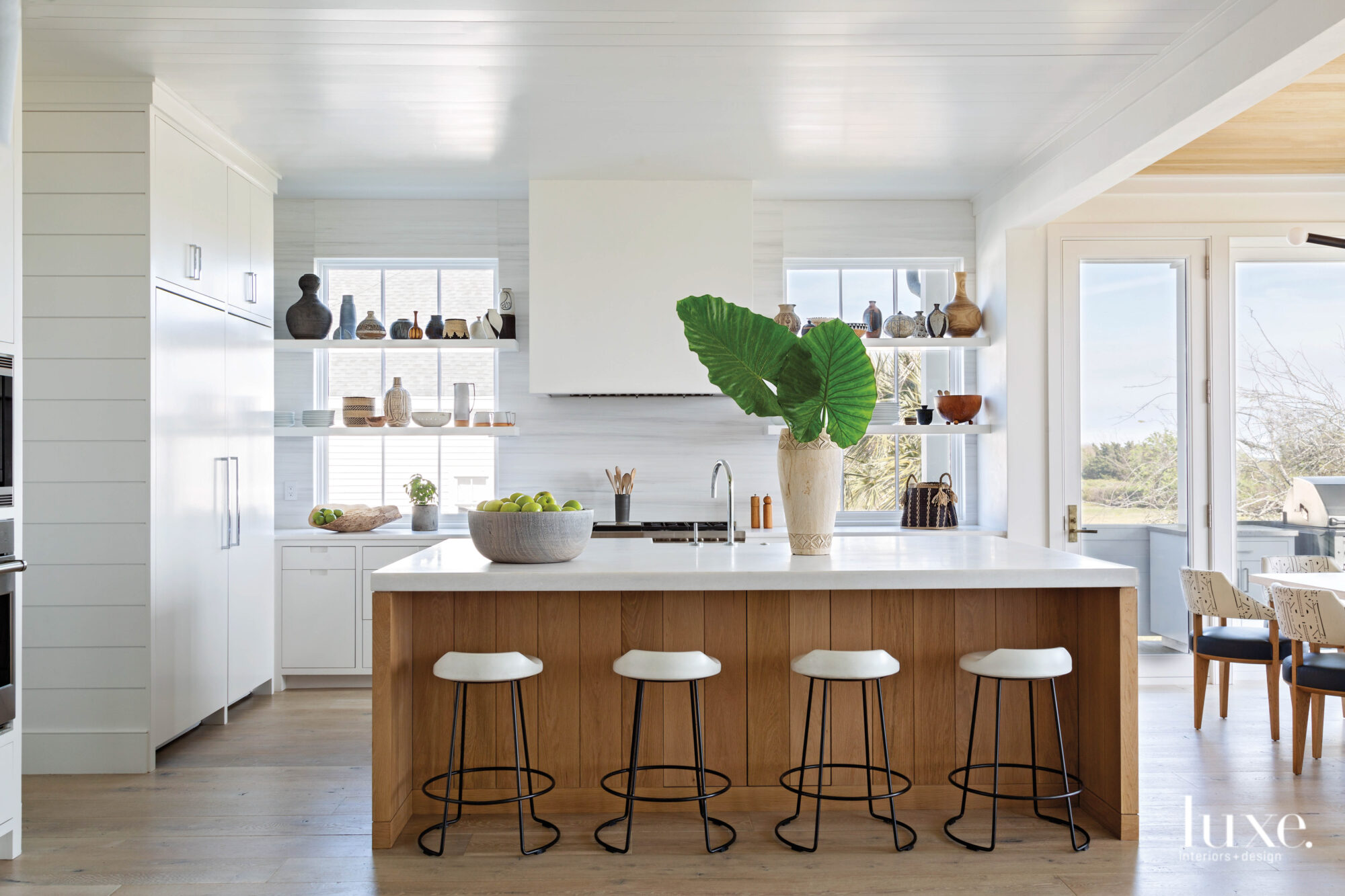 White kitchen with maple island,...