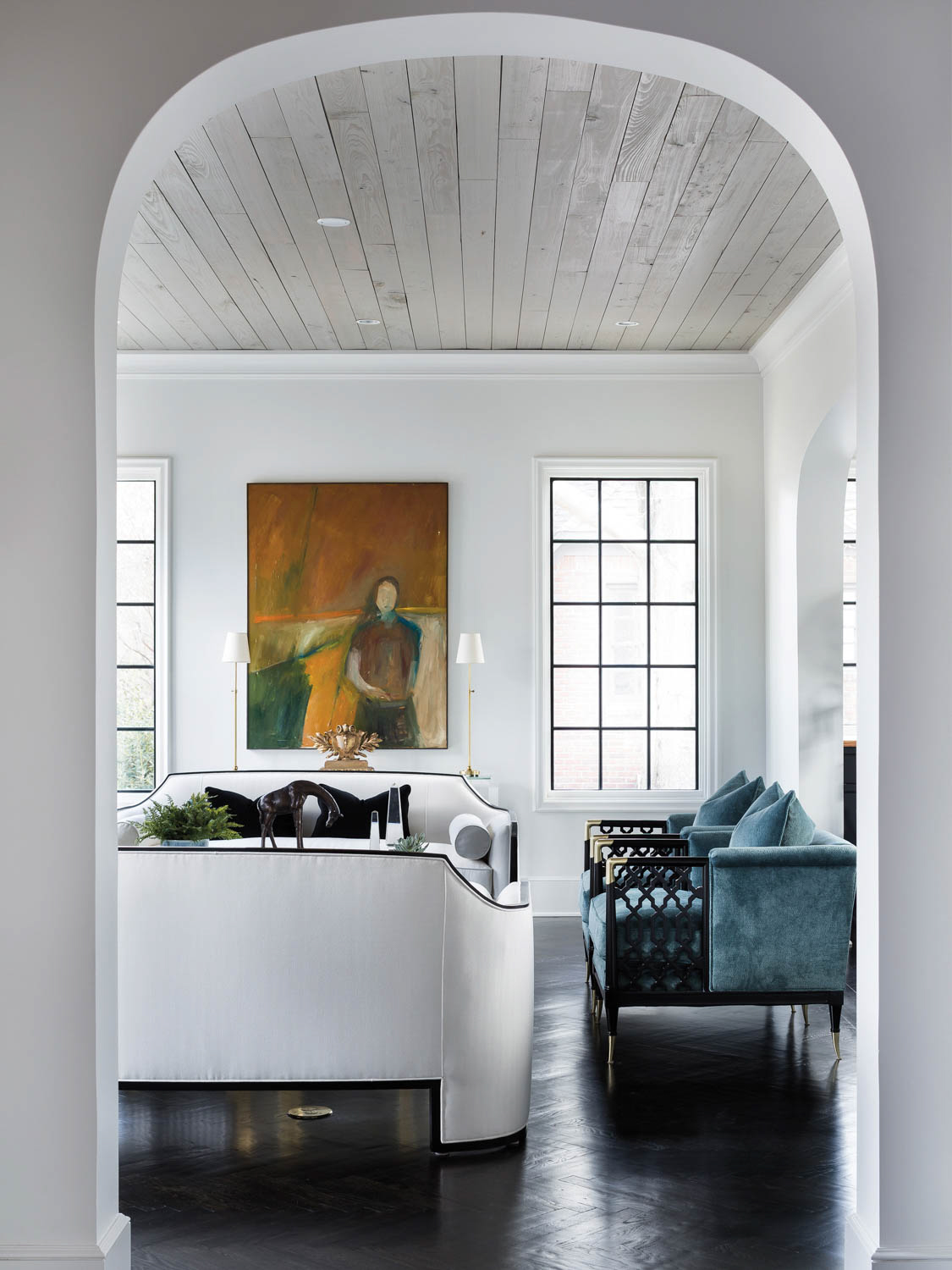 entry into a living area with blue sofa and white chair