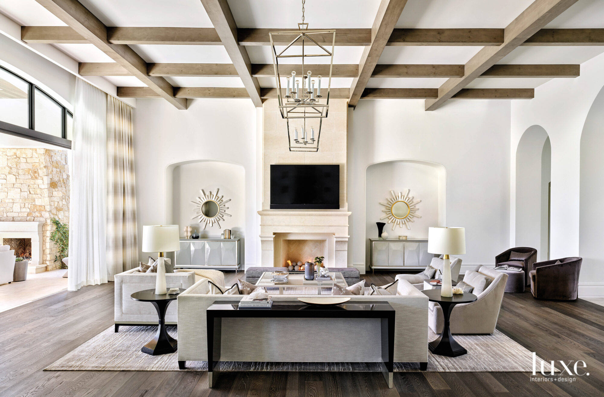 The neutral living room has wood beams, white walls and archways.