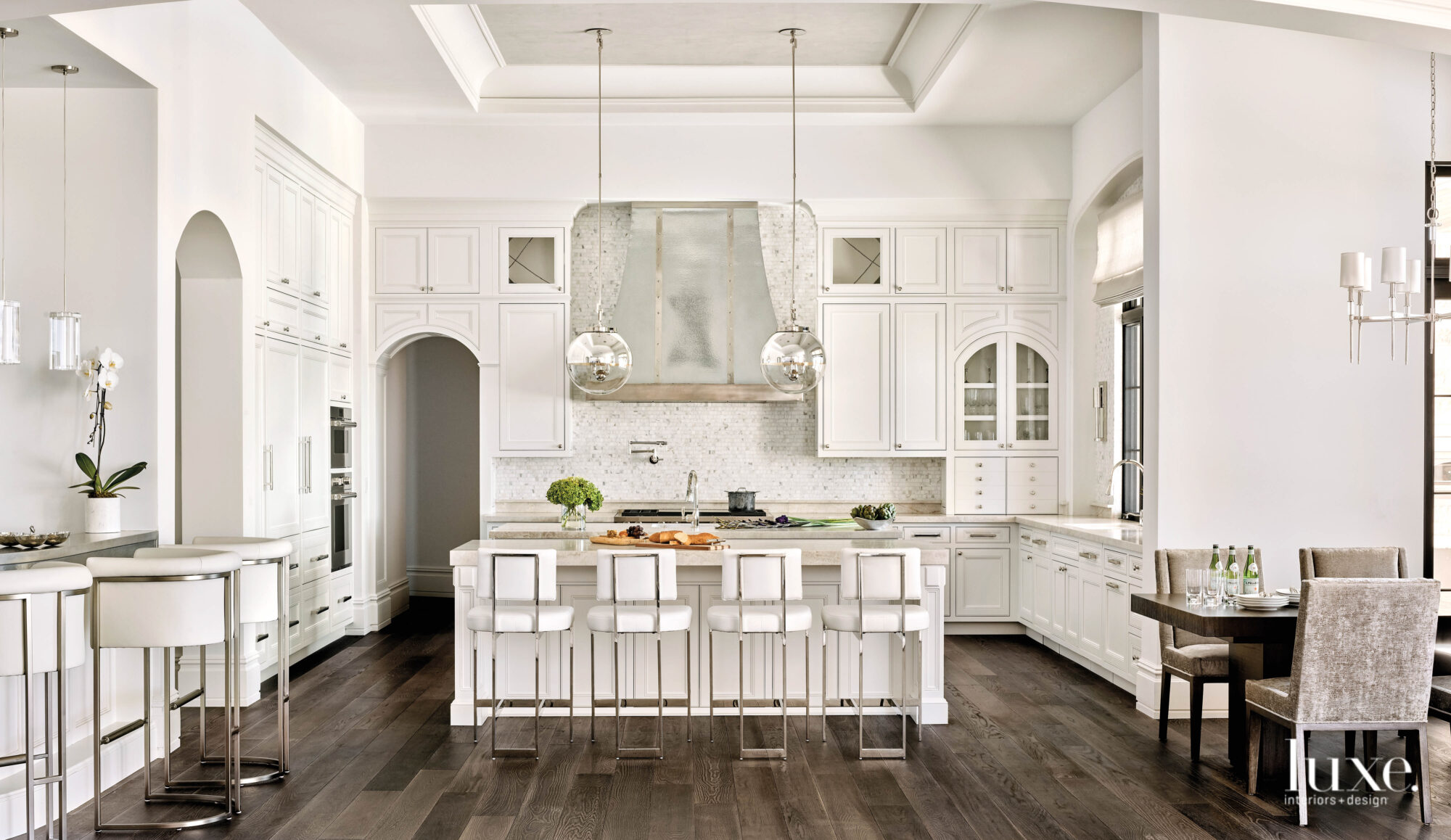 The all-white kitchen features a...