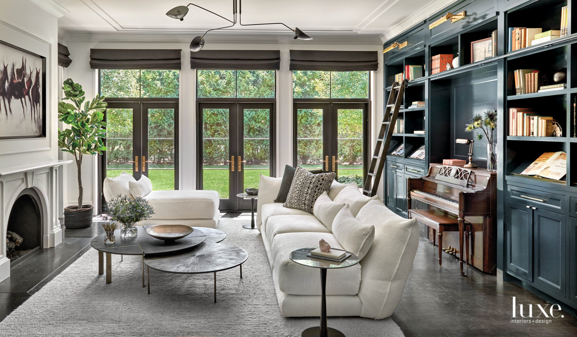 The living room with built-in cabinetry along the back wall painted in a gray-blue tone.