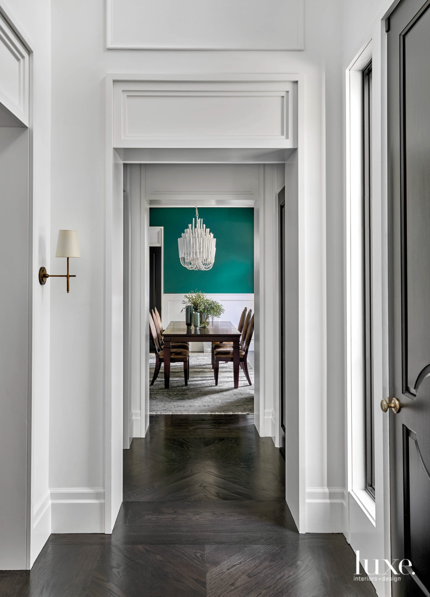 Dining room with teal green walls and a chandelier over the dining table.