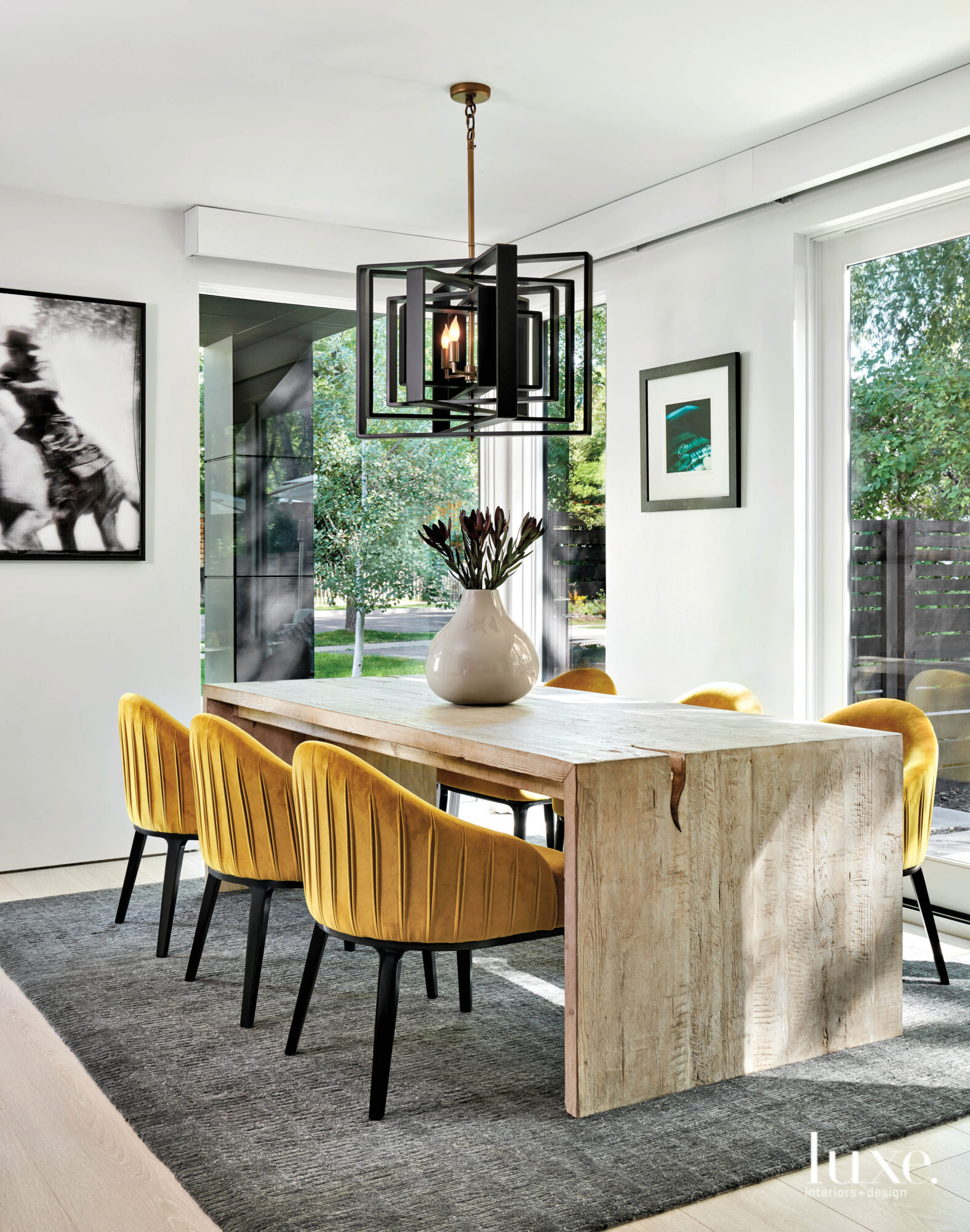 A dining room features mustard-colored chairs and a modern light fixture.