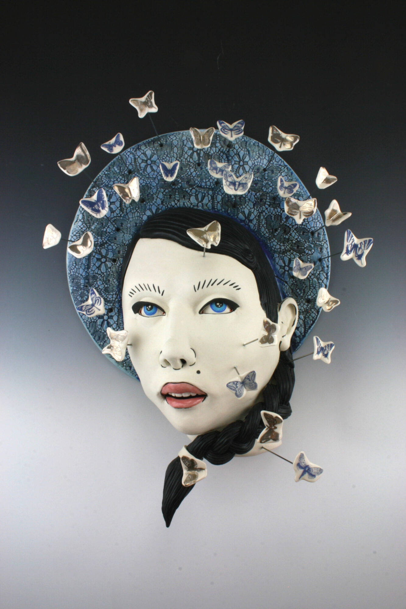 Ceramic artwork of woman's face and butterflies