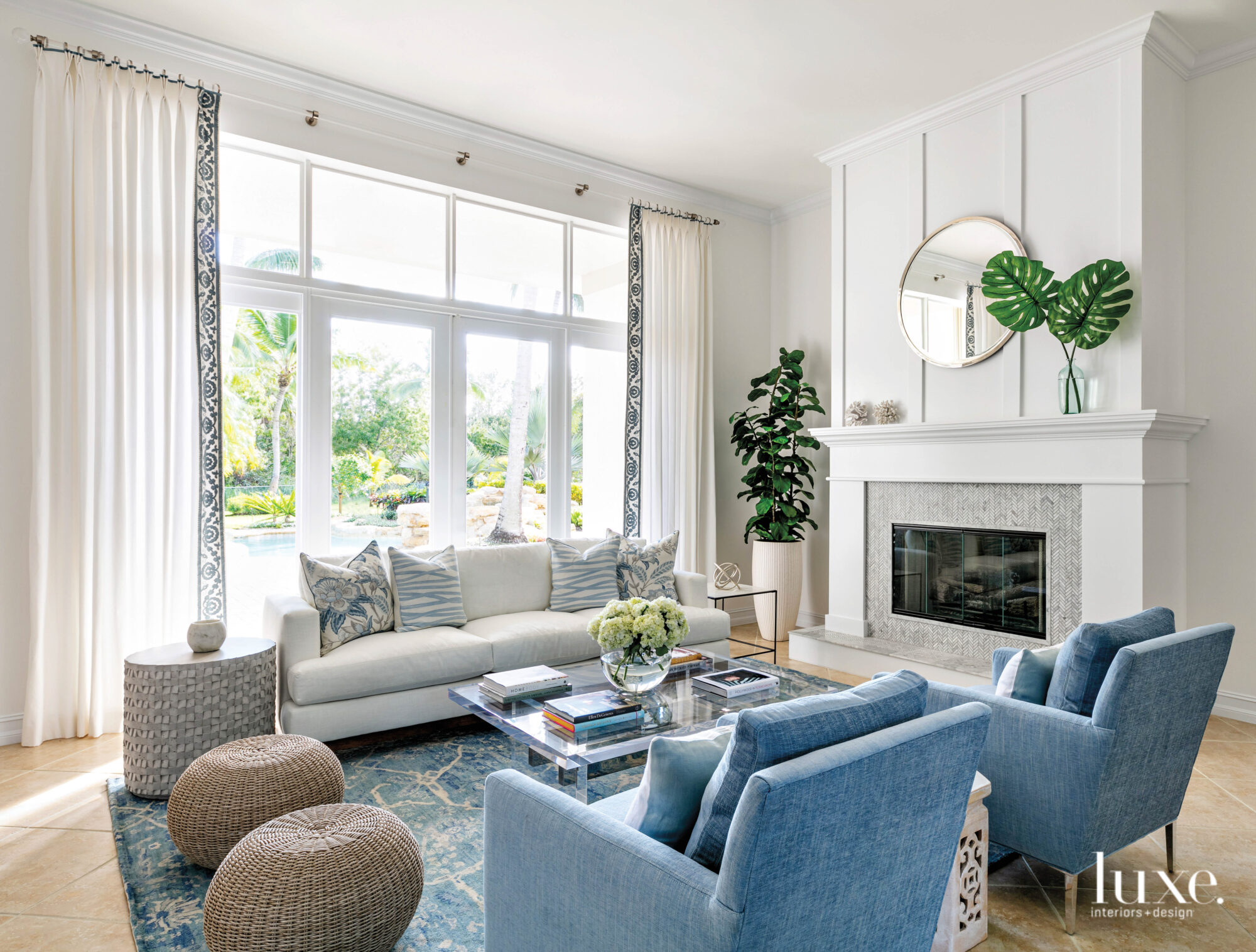blue and white living room with armchairs, sofa and fireplace