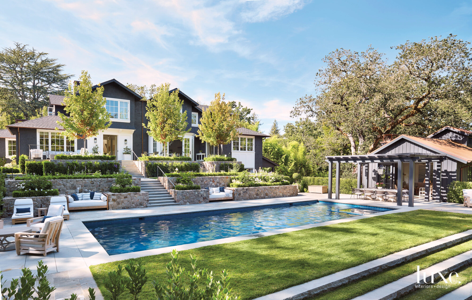 The exterior has lush green plantings and a pool.