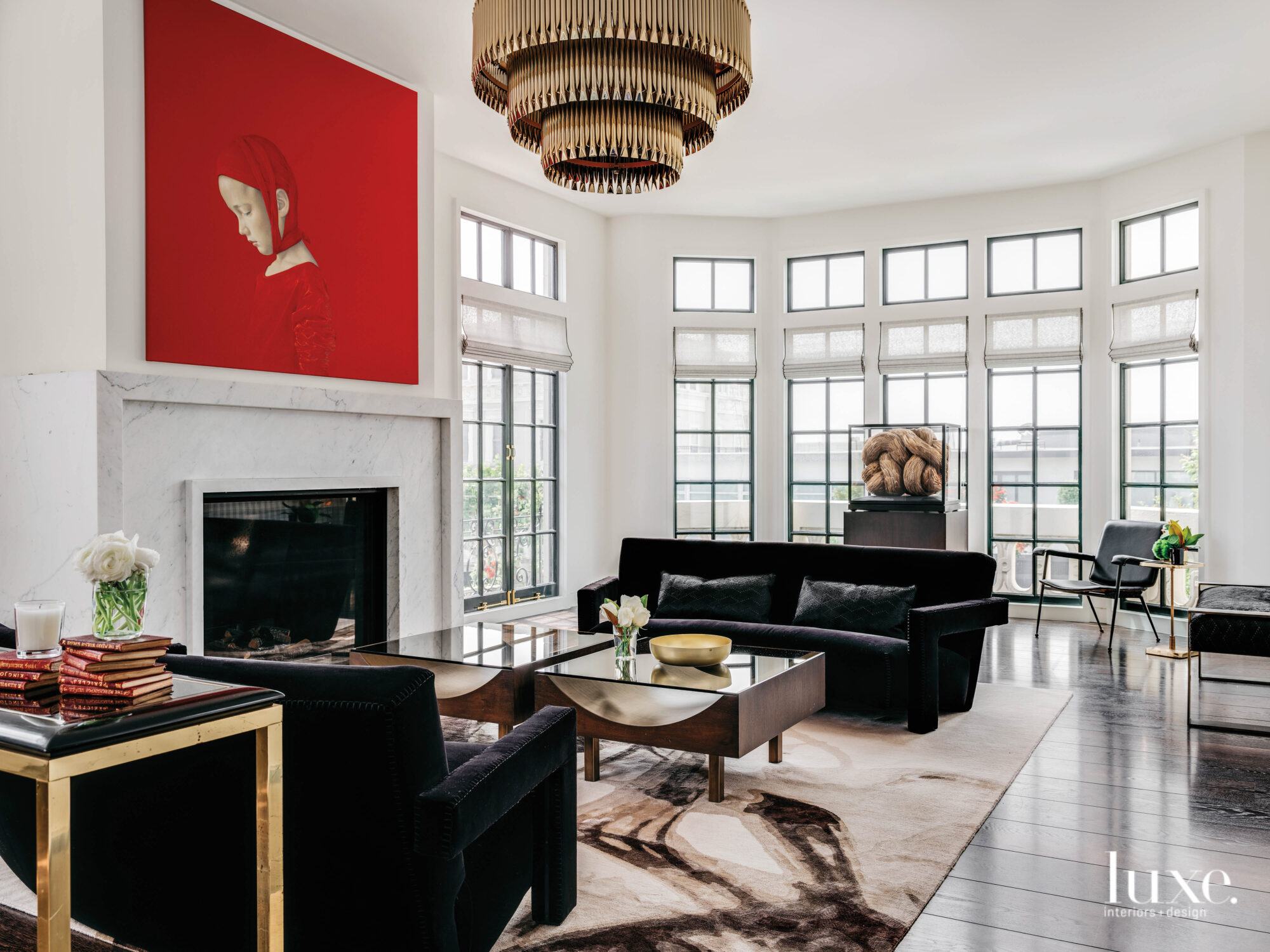 A living room is done in black and white tones with an artwork adding a splash of red.