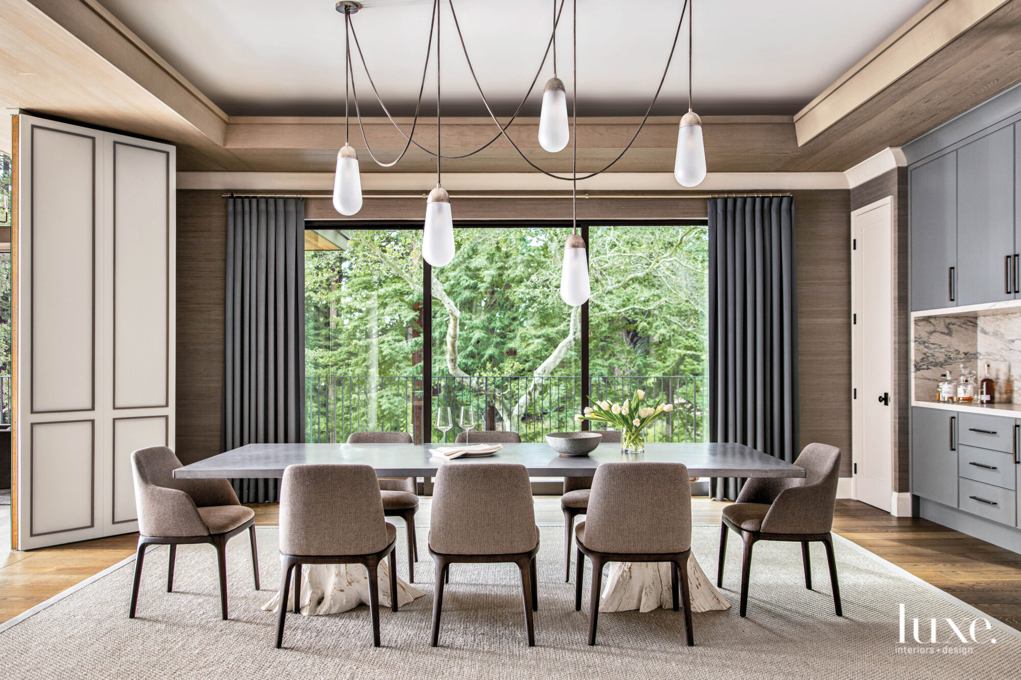 A dining room has soft neutral colors and a long table and many chairs.