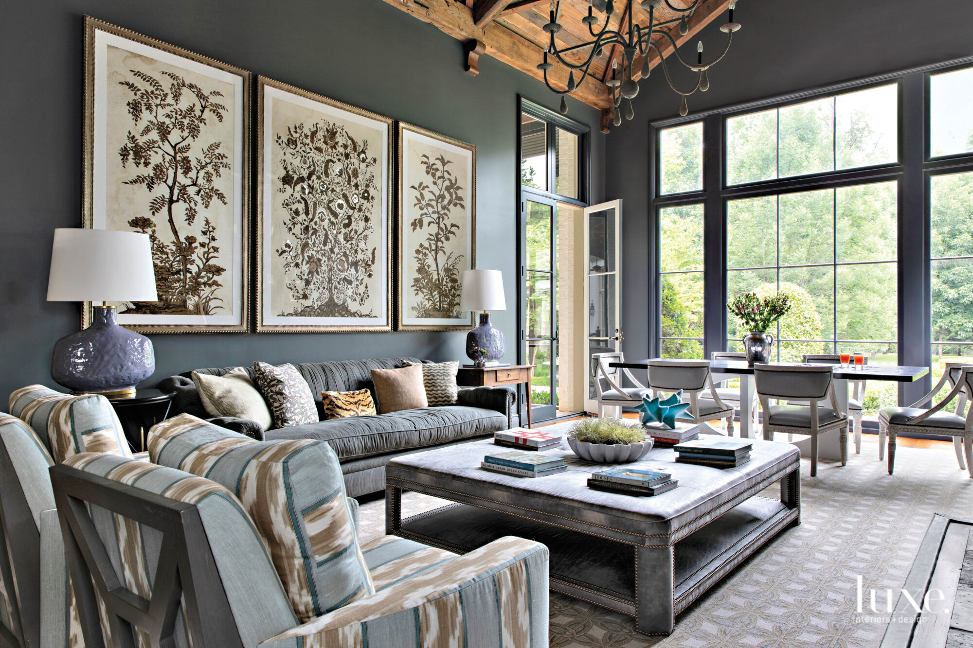 Family room with dark gray walls, florid artwork, wood ceiling, big windows