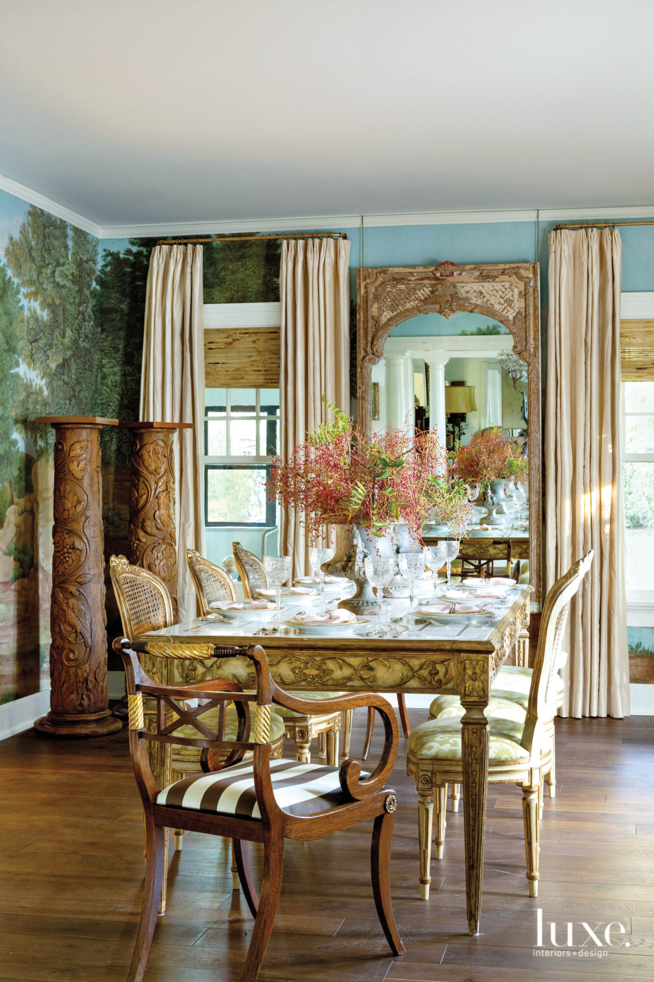 Dining room with scenic wallpaper, tall mirror and pair of carved pedestals