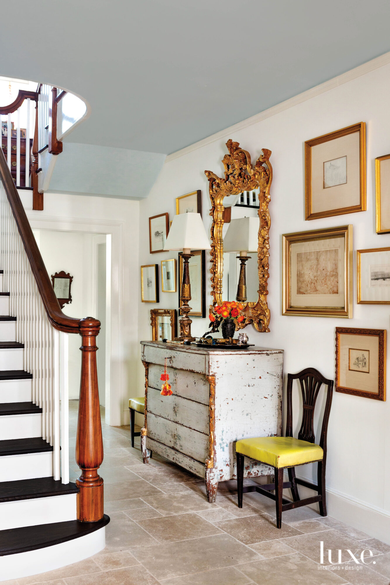 Hallway with stairwell, chest and framed pictures on the wall
