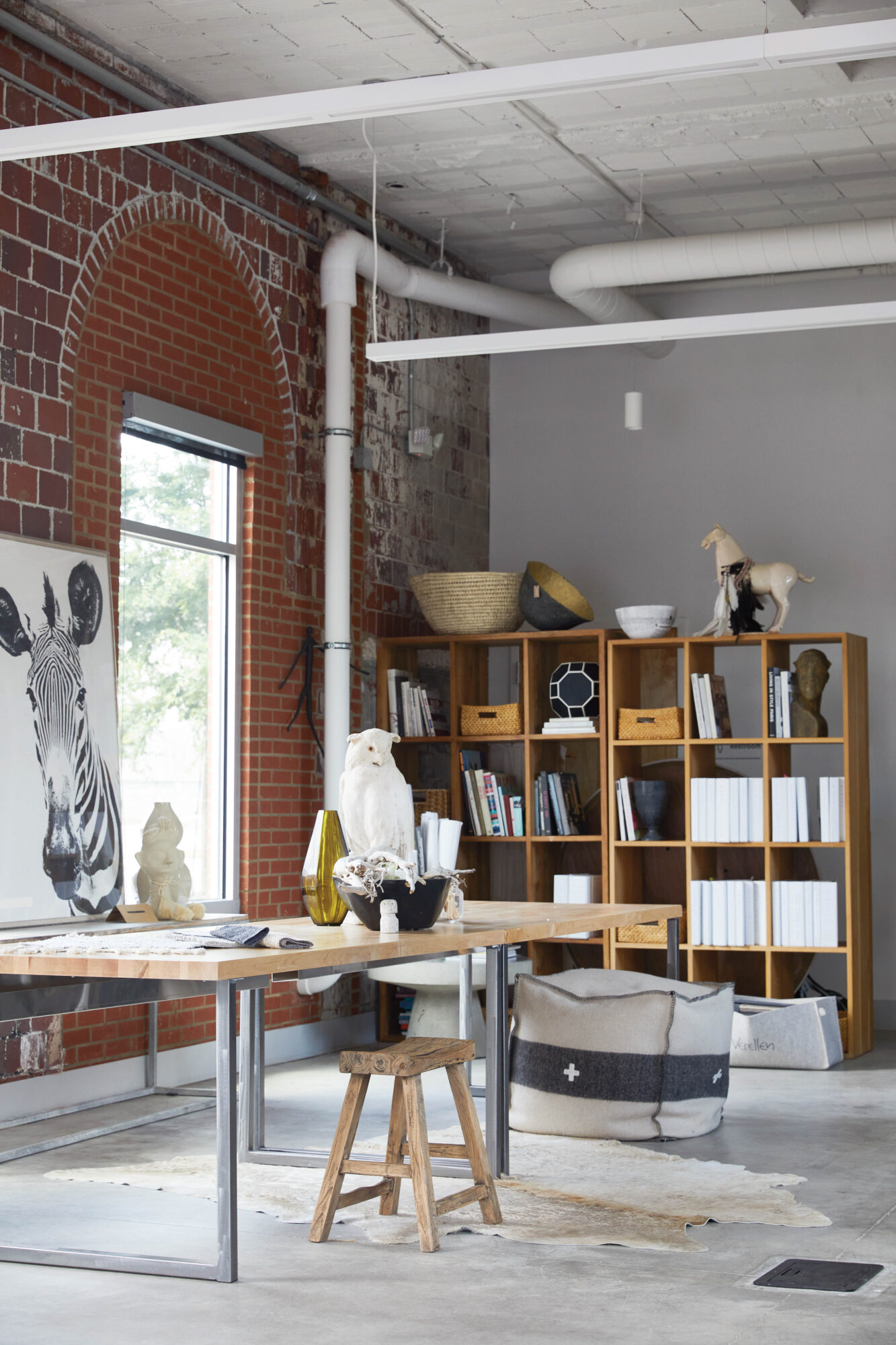 Loft-style office with exposed brick, open shelves and zebra artwork
