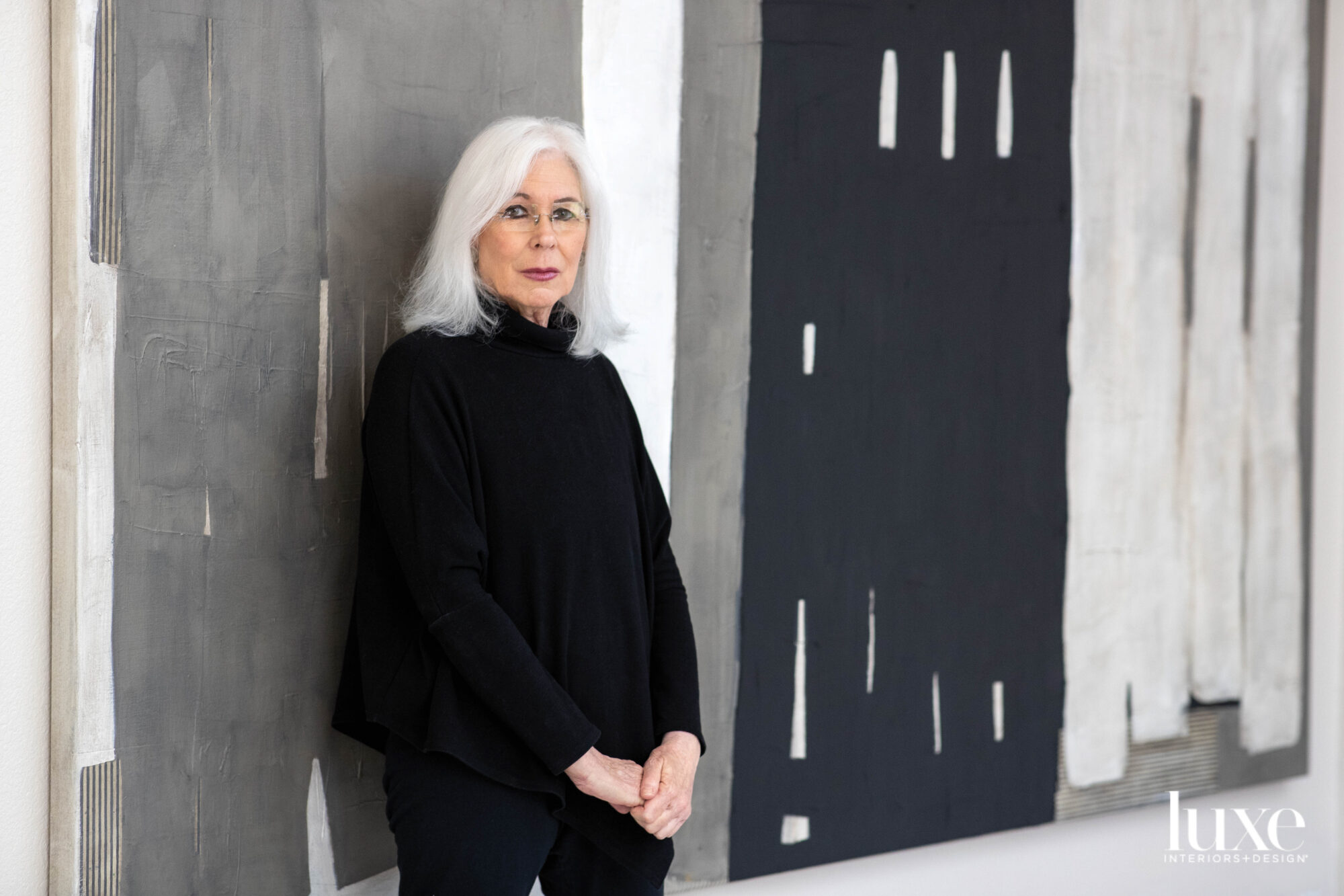 The artist stands in front of a large gray-white-and-black painting.