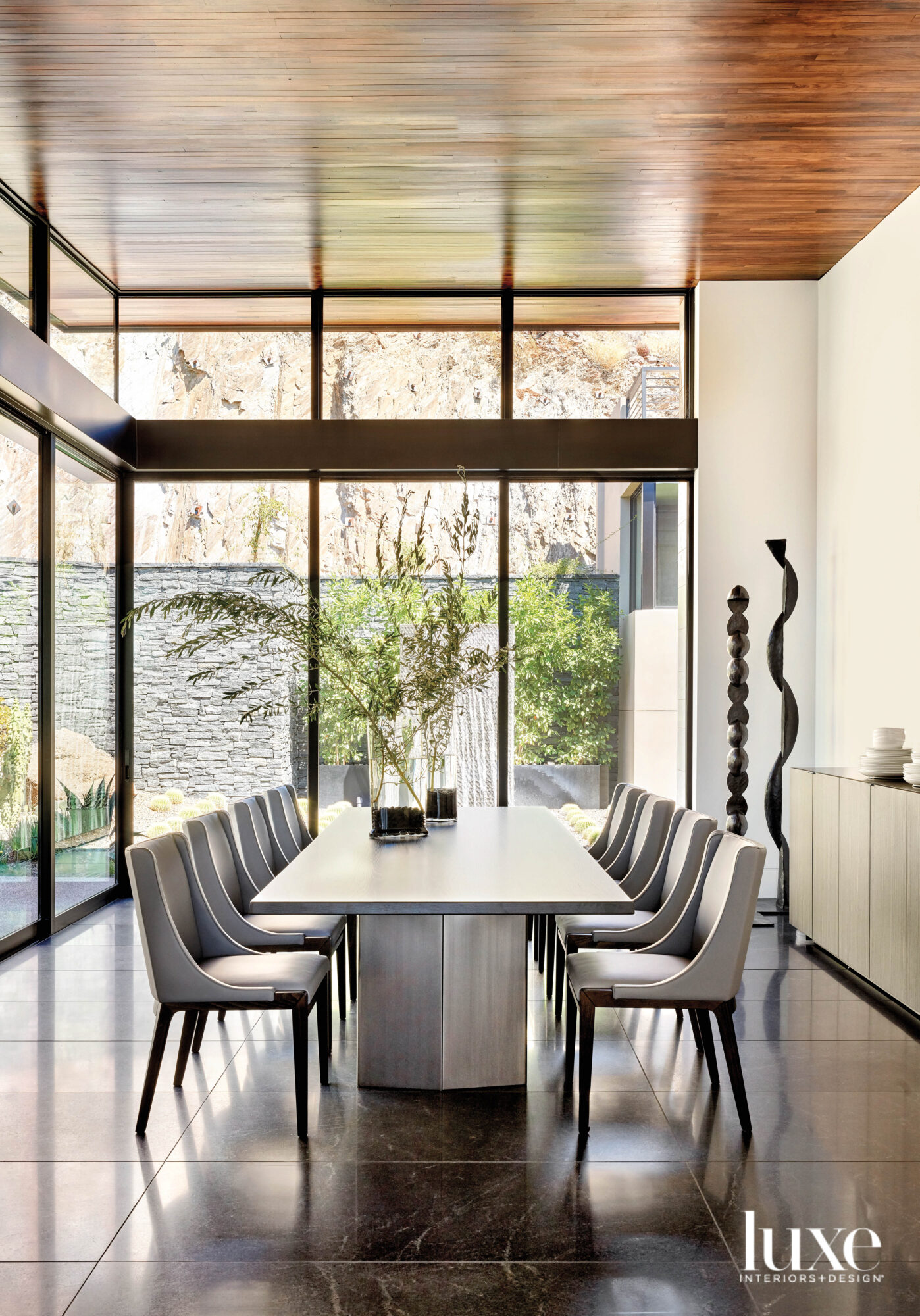 A dining room with stone floors that looks out on to a garden.