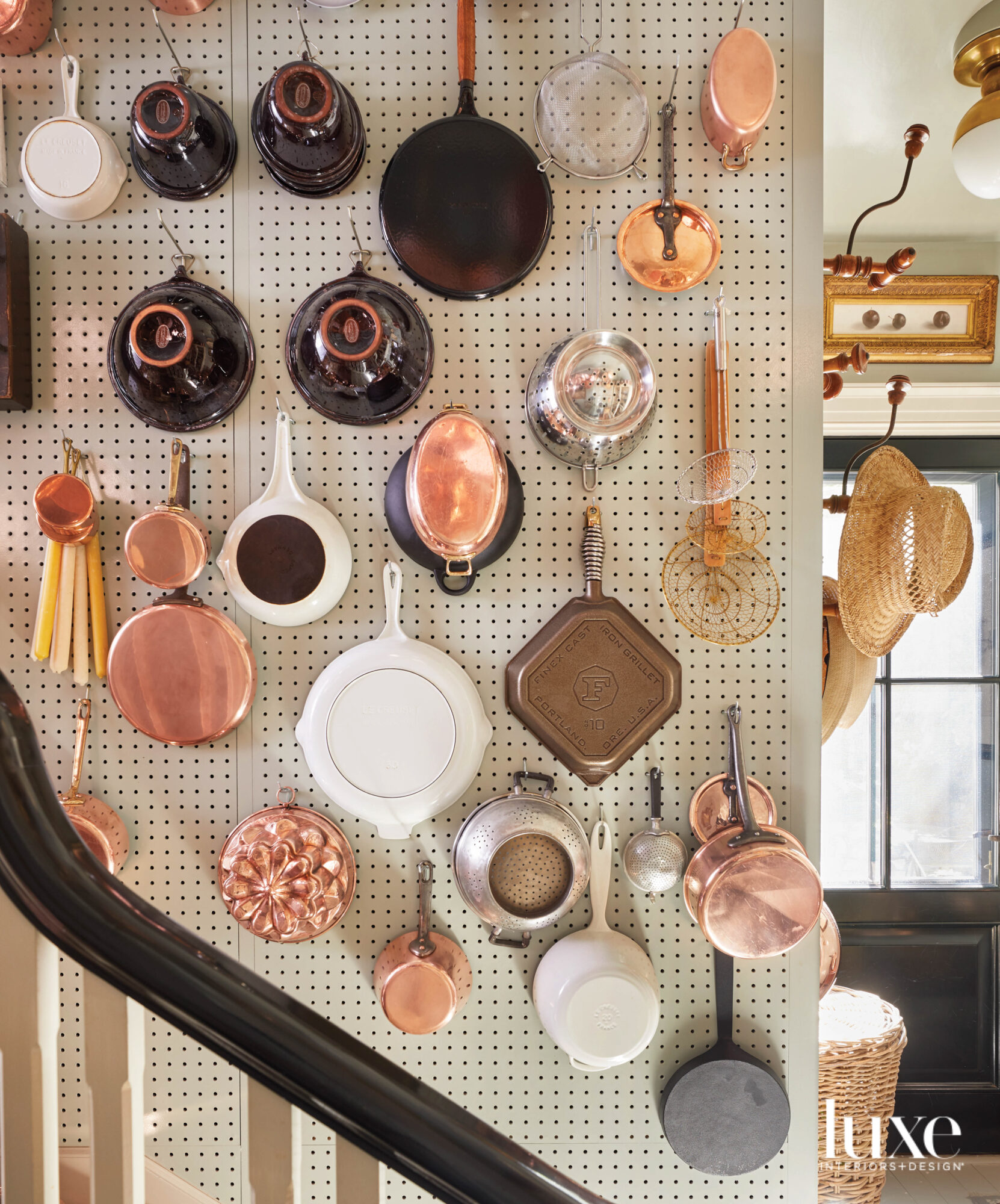 pots and pans on wall above stairs