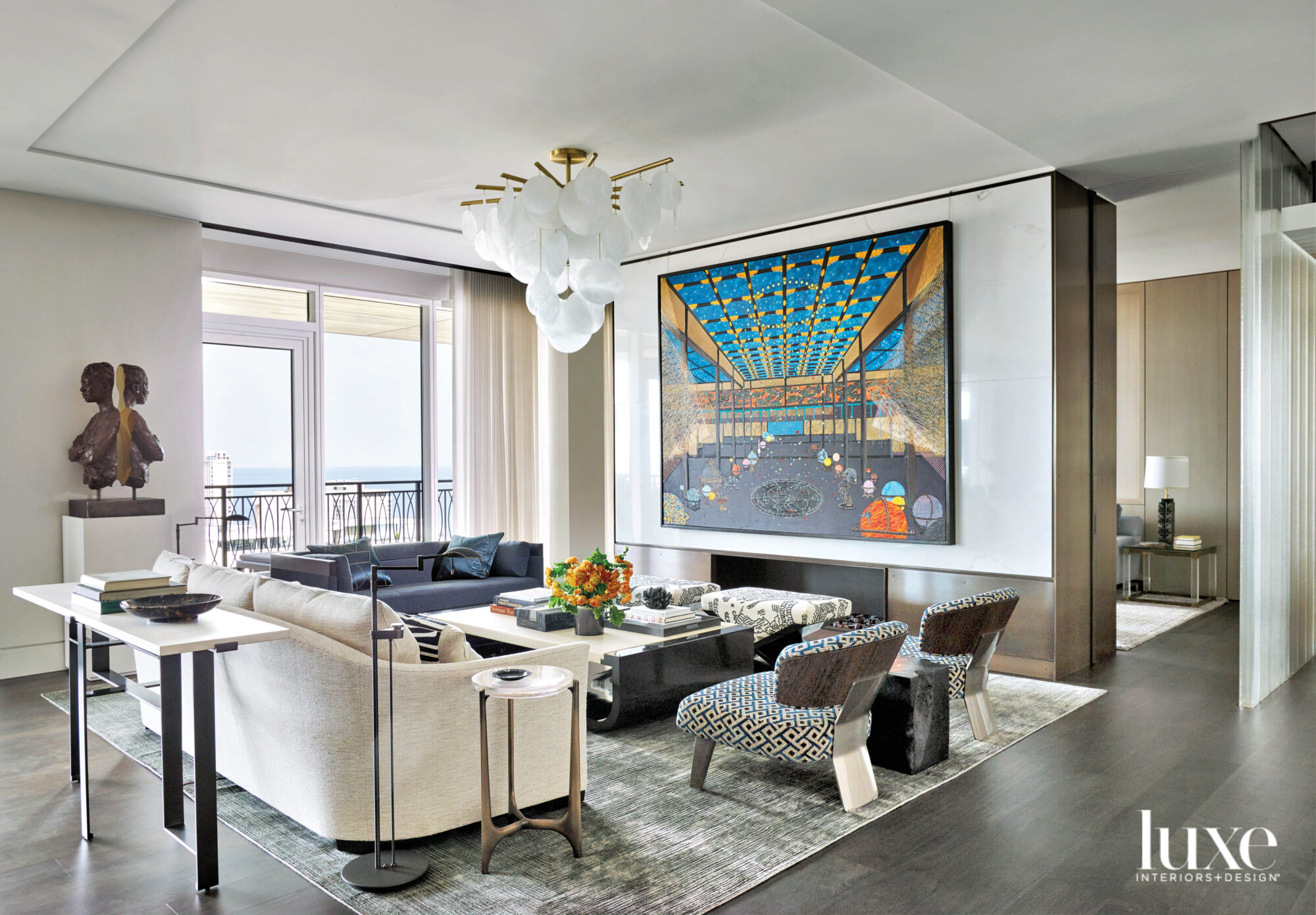 A living room with black-and-white furniture and a large colorful painting over the fireplace.