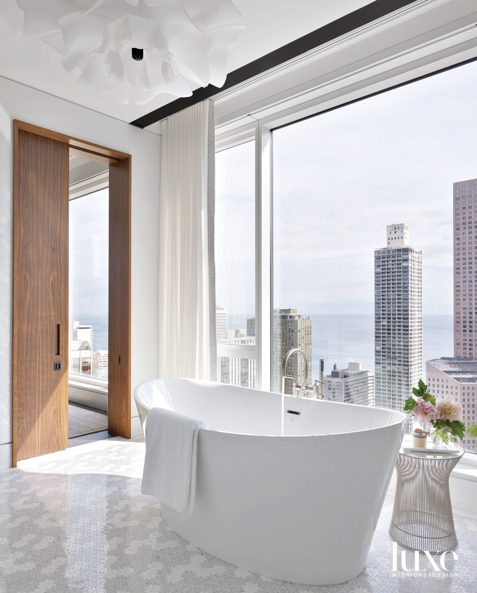 A freestanding white bathtub looks...