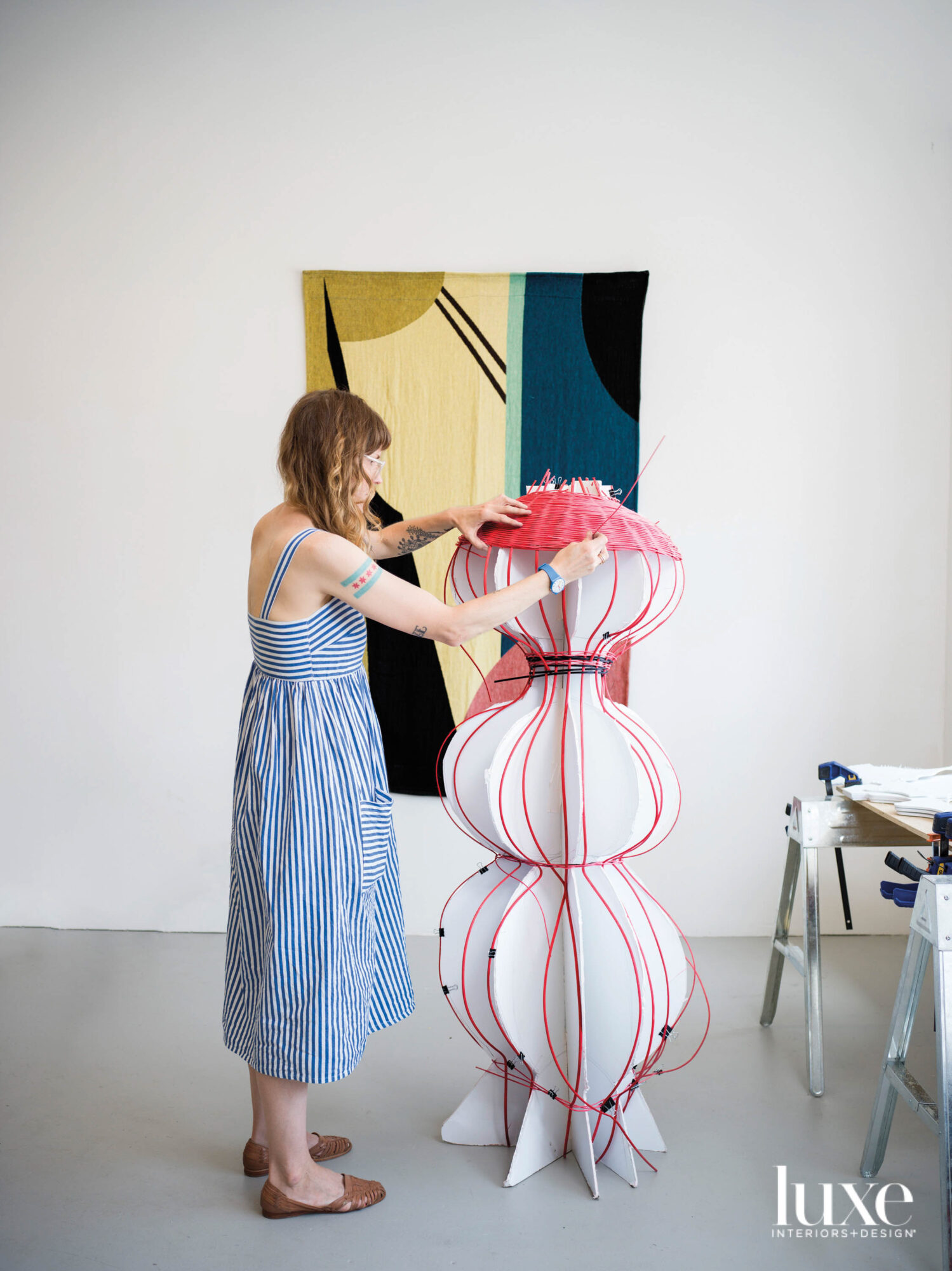The artist weaving a large pink basket. A textile hangs on the wall.