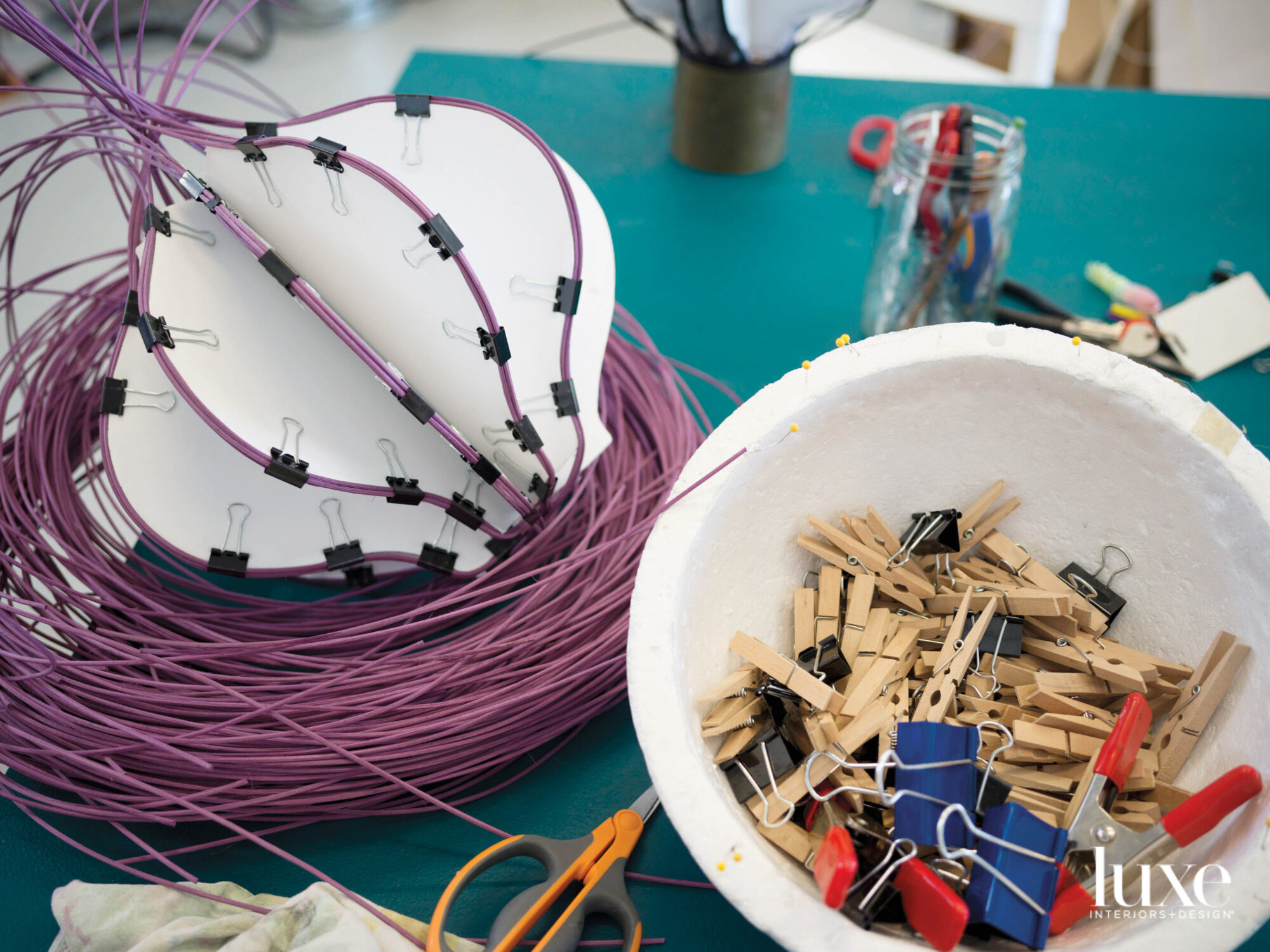 Purple fiber to be woven into a basket, clothespins and binder clips.