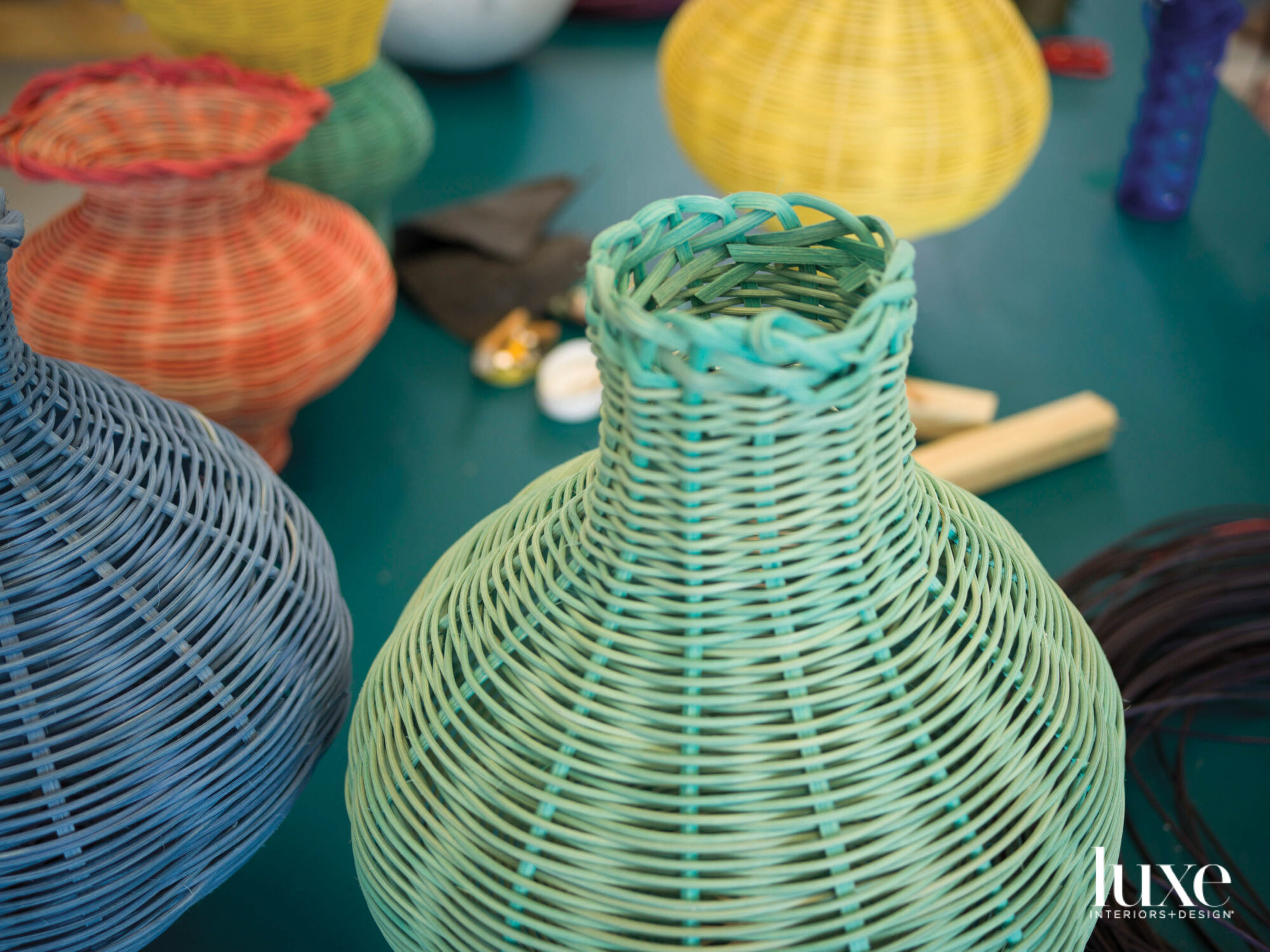 Blue and green woven baskets with orange and yellow ones in the background.