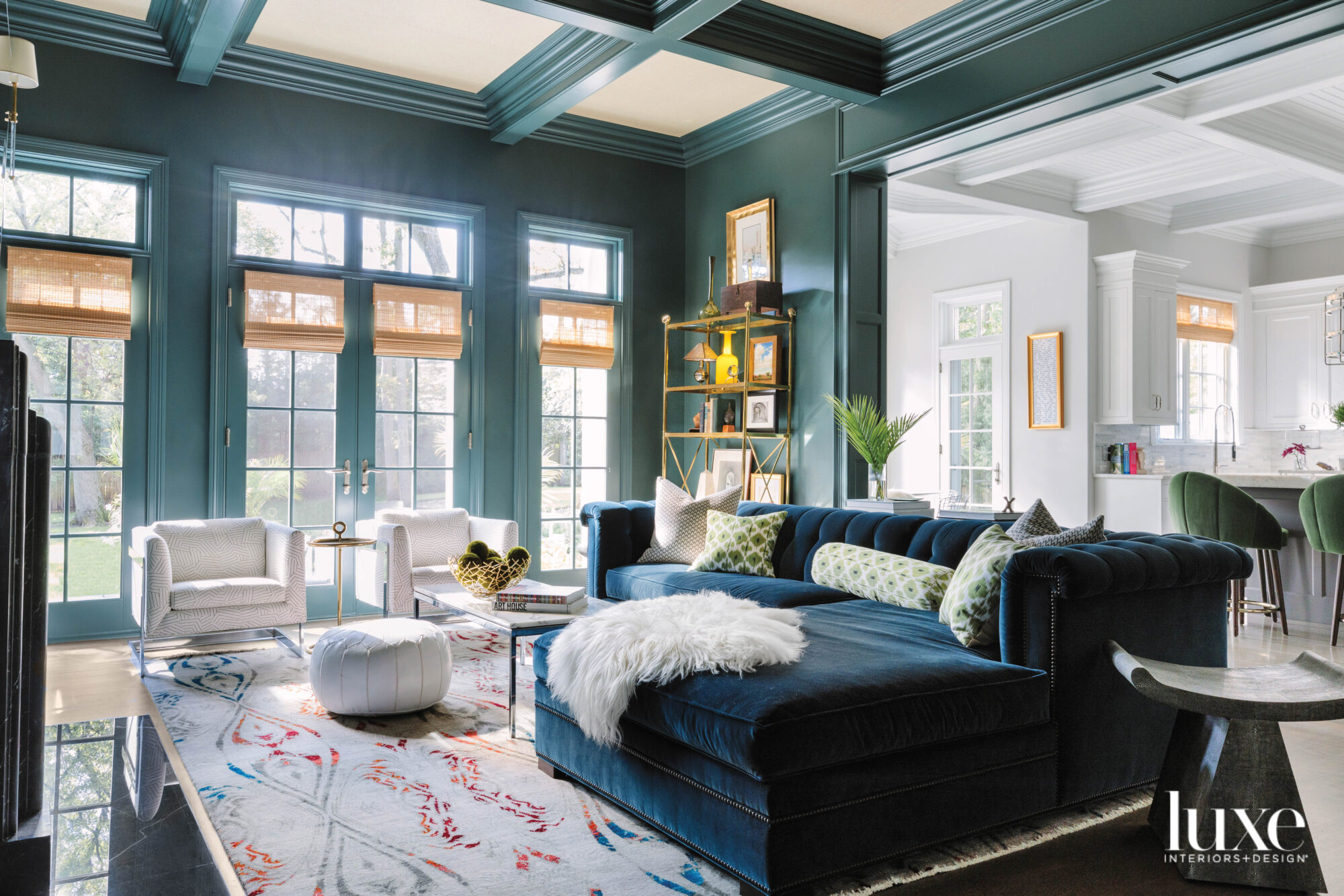 The family room has a a dark teal sectional. The walls and the ceiling beams are painted green.