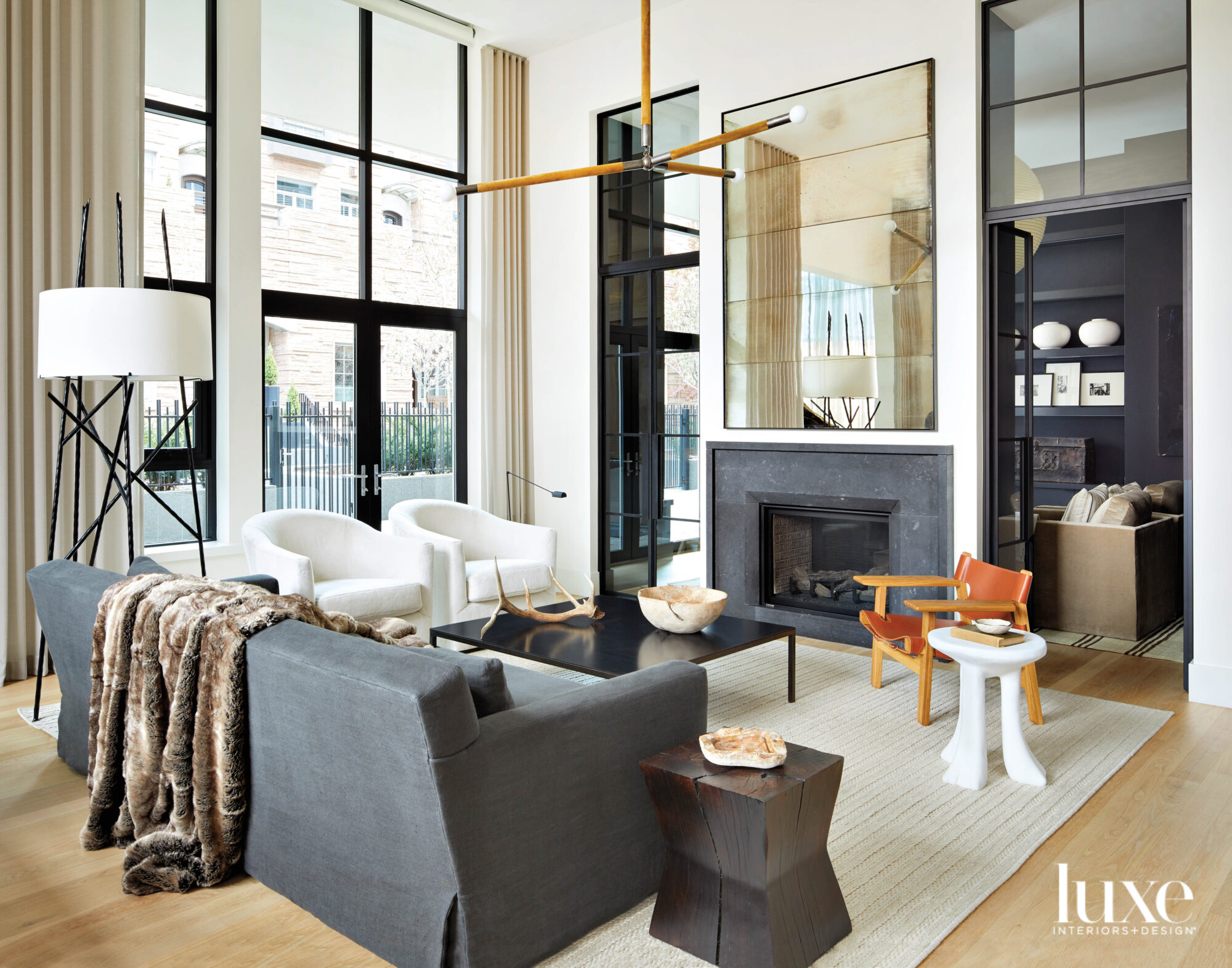 A living room is arranged around a fireplace composed of black stone and mirrored panels.