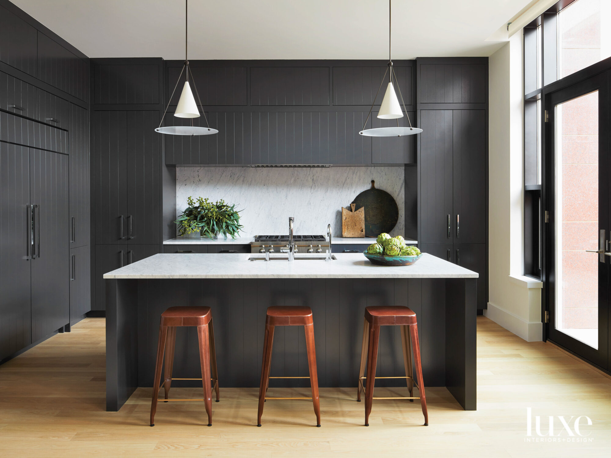 A kitchen has black cabinetry...