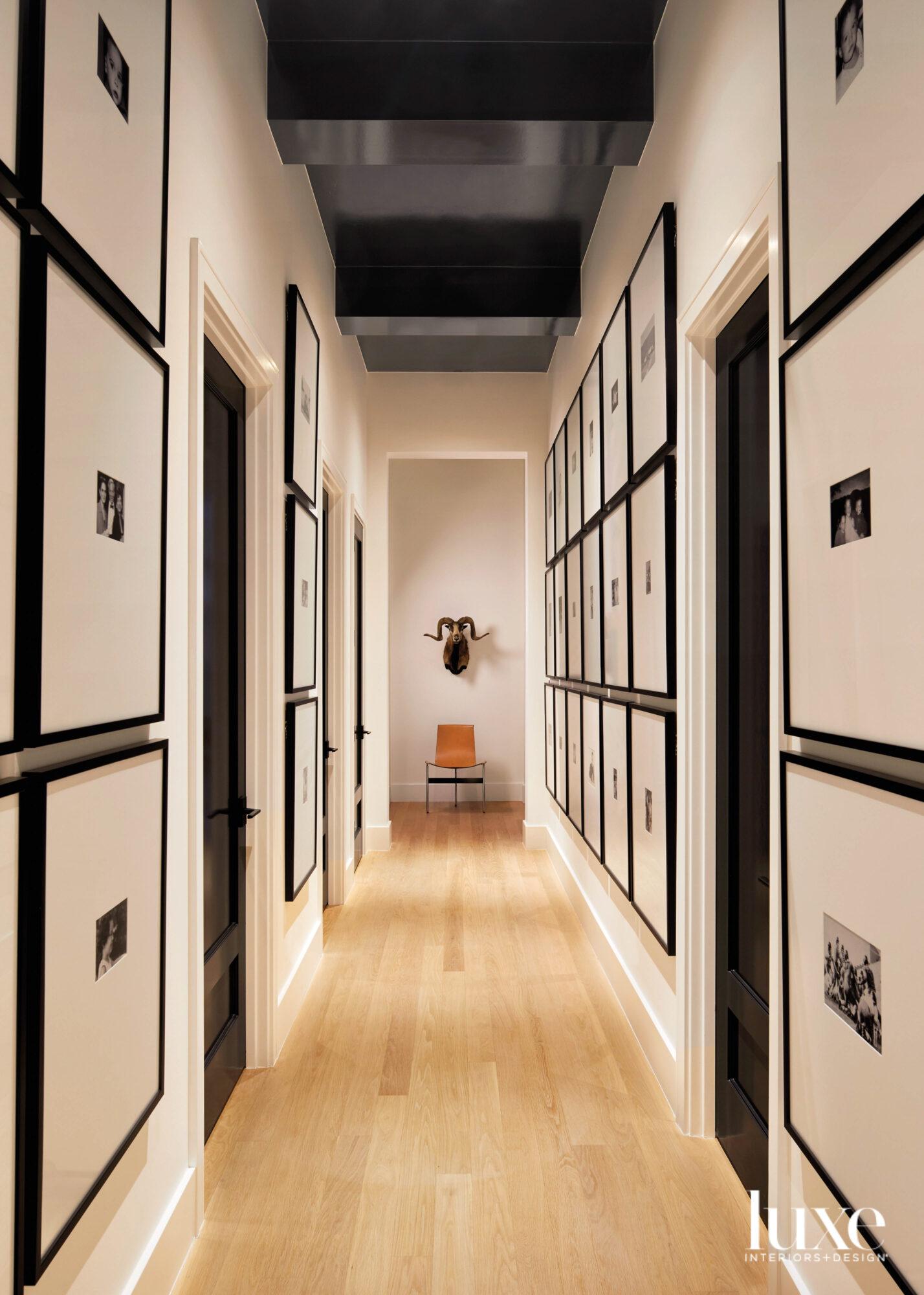 A long hallway features framed...