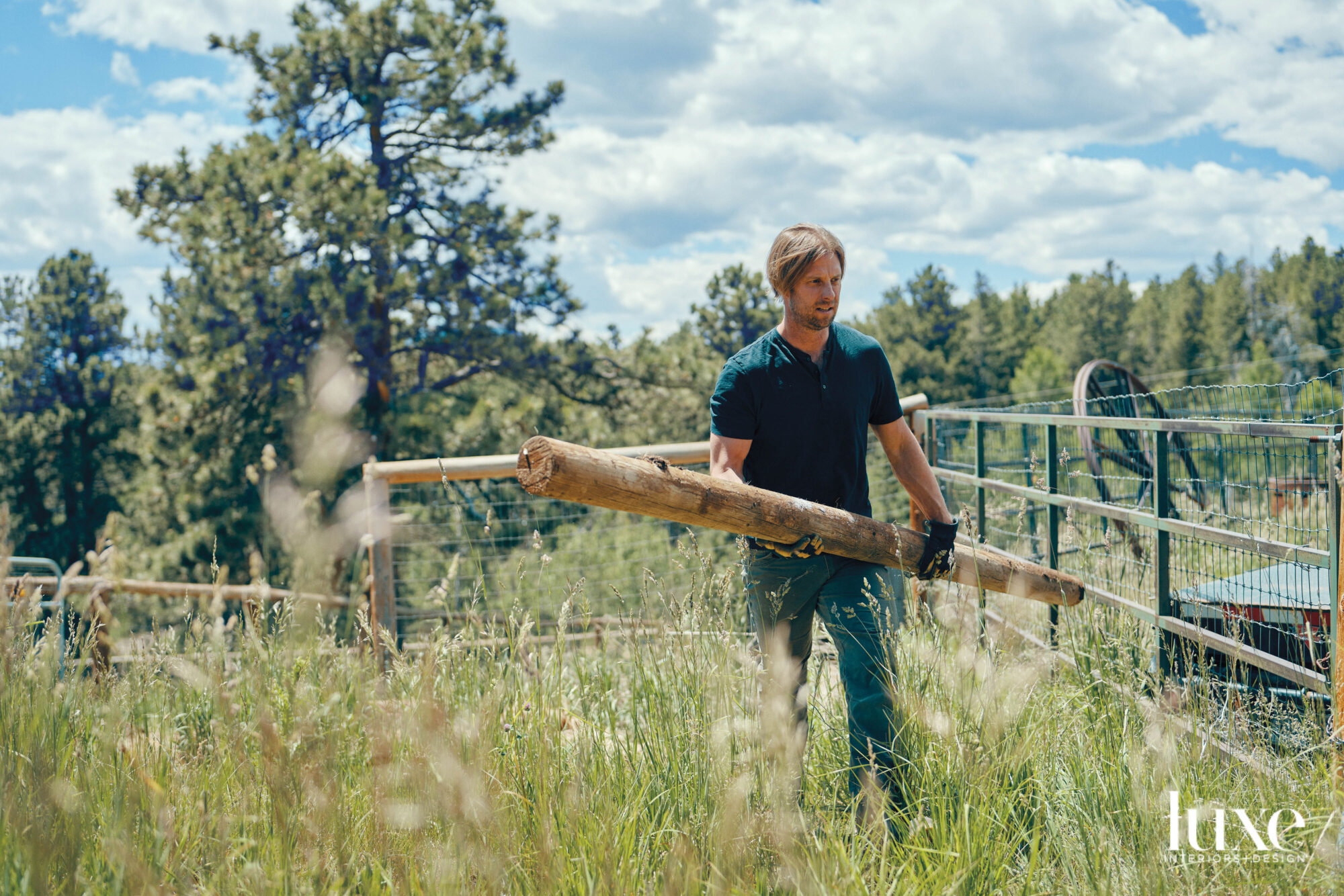 The artist carries a log outside of his studio.