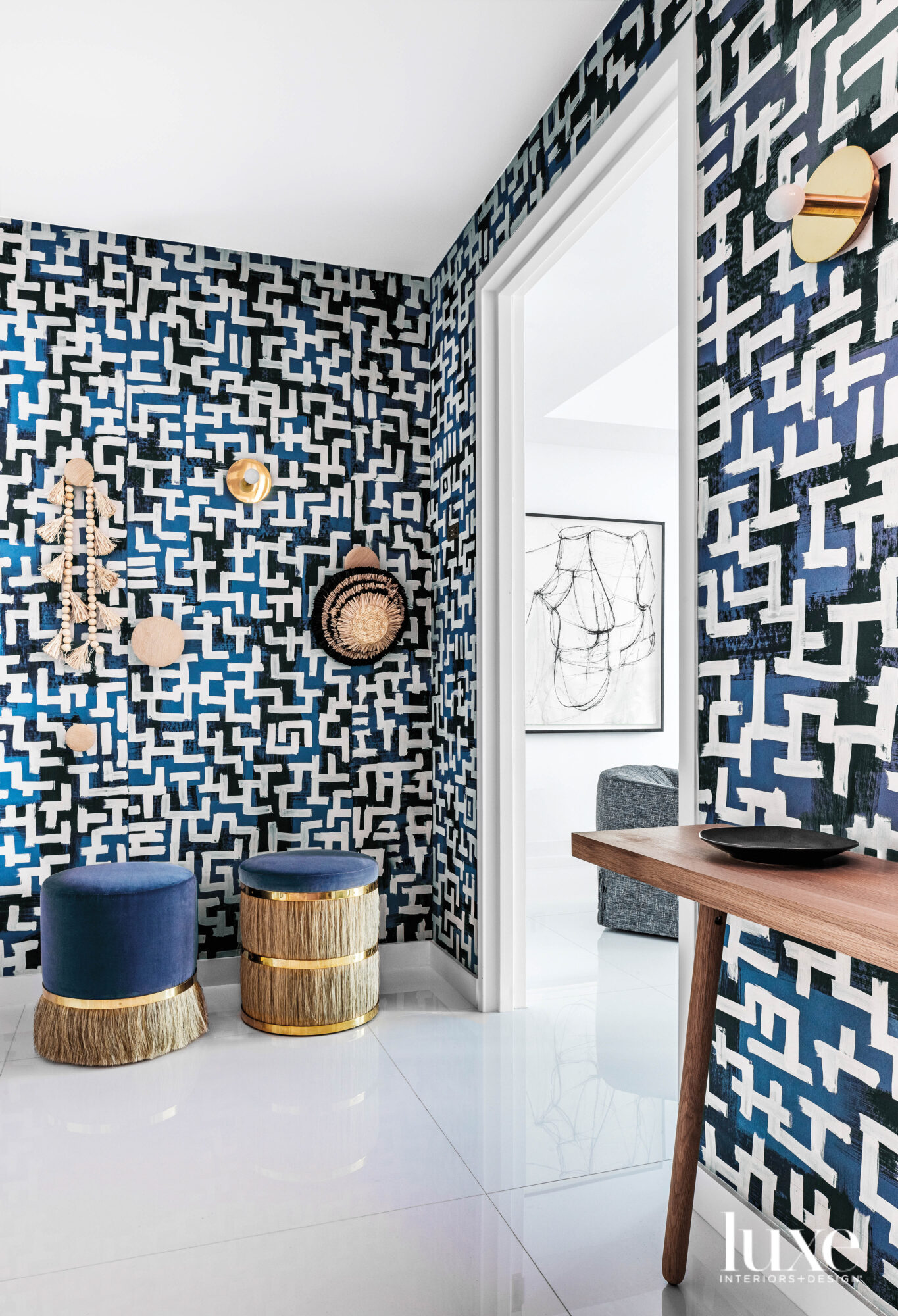 entry with graphic blue wallcovering, gold wall sconces and two stools