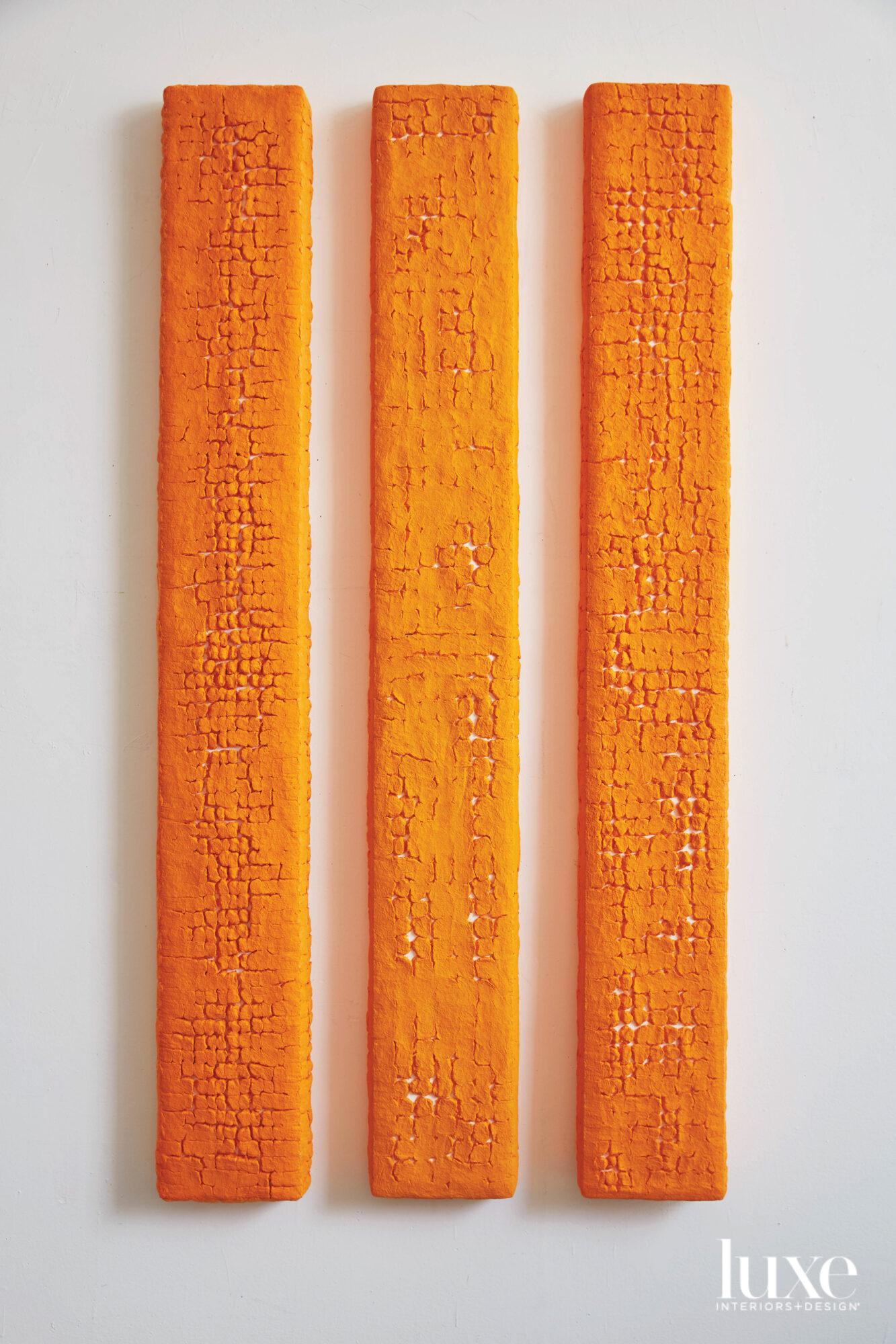three orange pieces of rosa's art