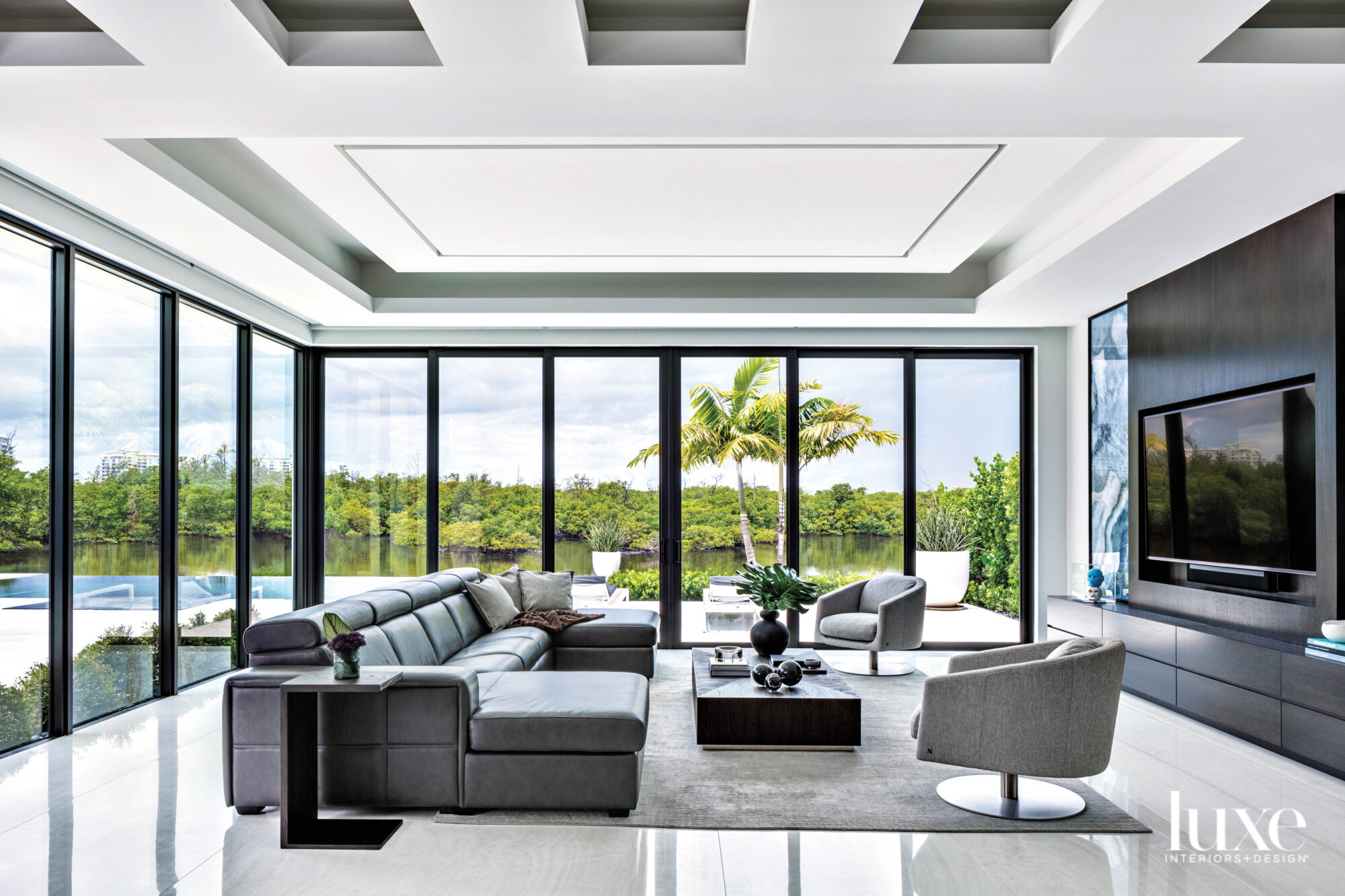 contemporary living area with white porcelain flooring, a gray sectional and water views