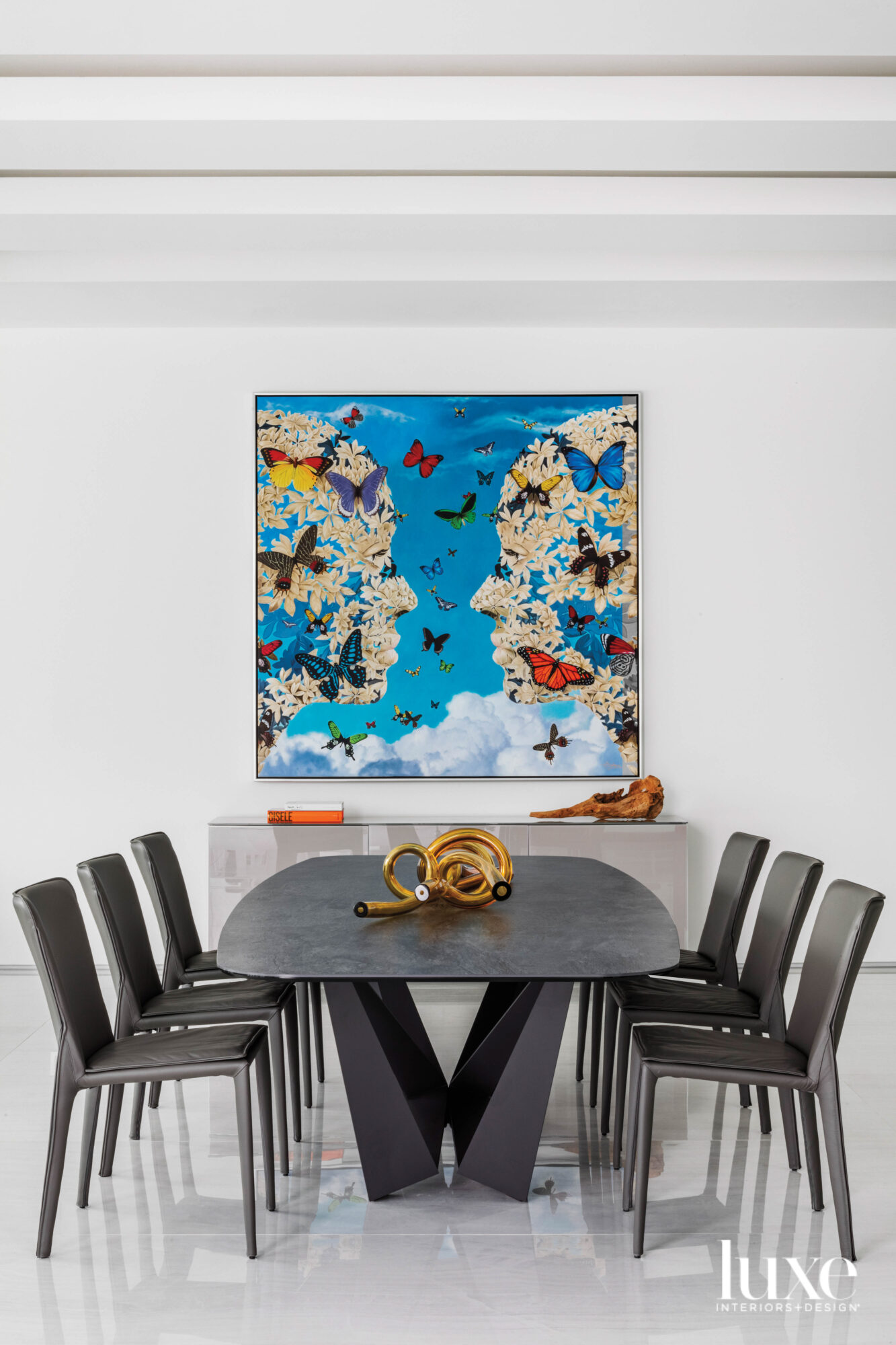 modern dining area with white porcelain flooring, a gray dining table and chairs and butterfly wall art