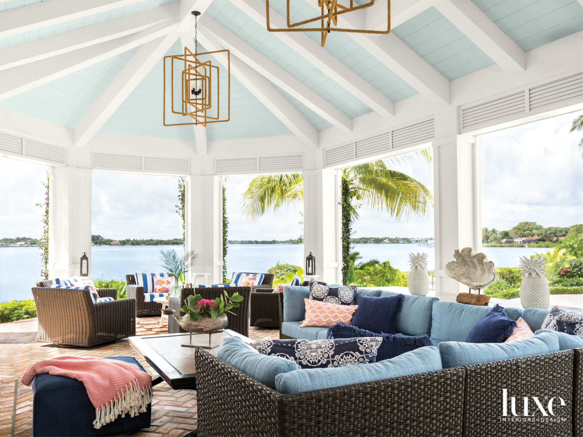 loggia overlooking waterway with light blue ceiling, rope lantern chandeliers and blue wicker furnishings