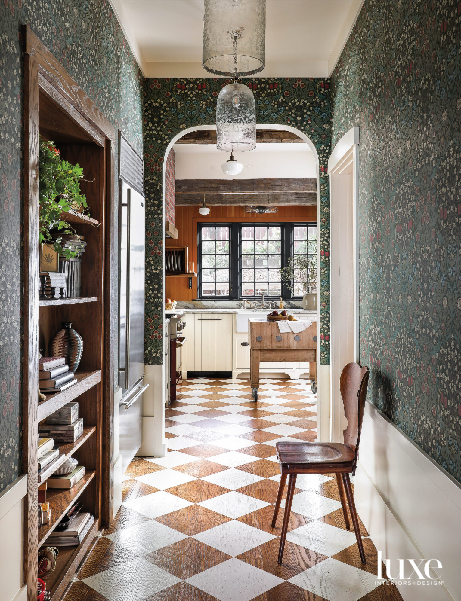 A hallway leading into a kitchen has a checkerboard pattern on the floor.