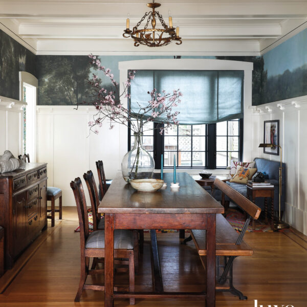 A dining room has a mural wallcovering around the top of the room.