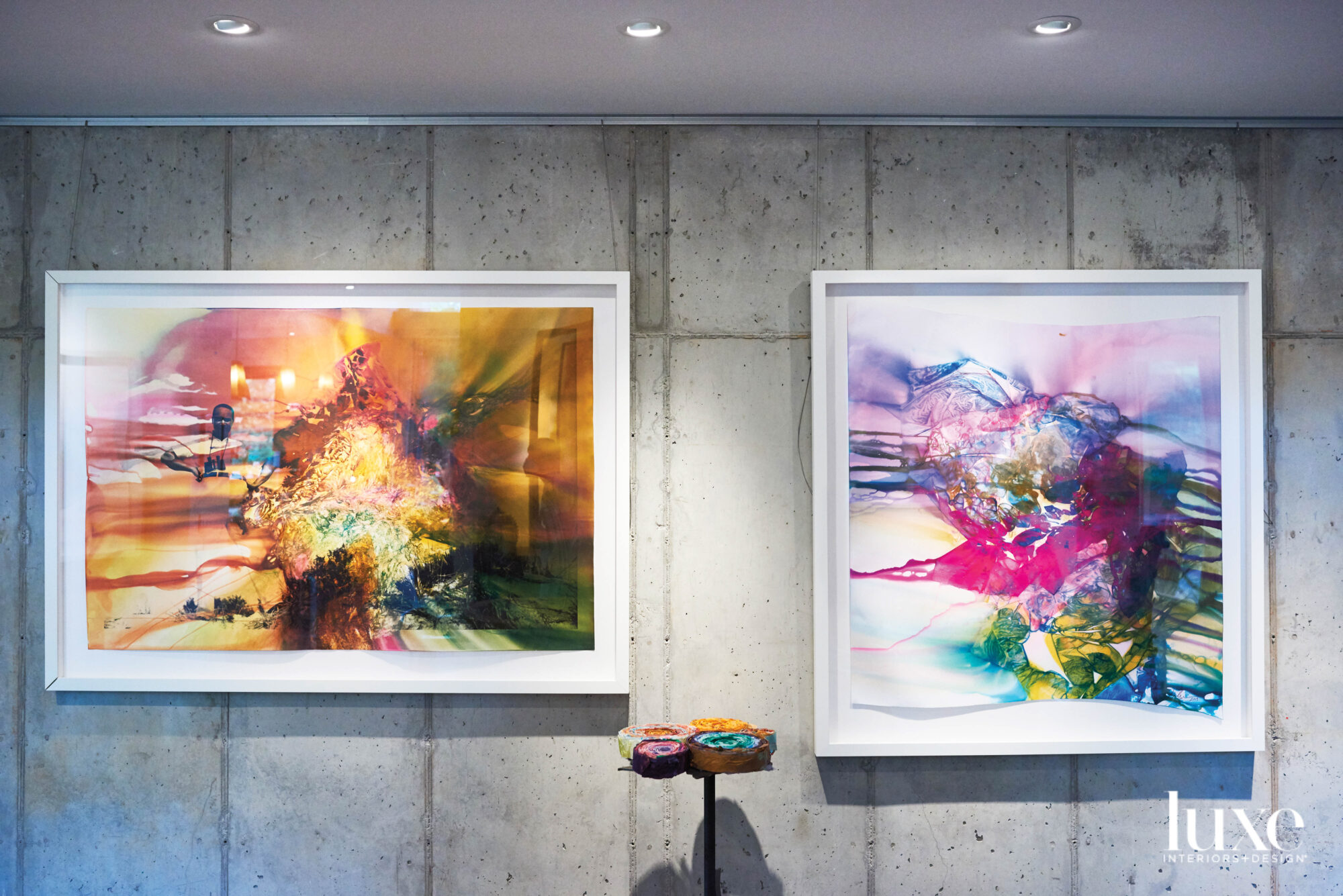 Framed artworks against a gray concrete wall