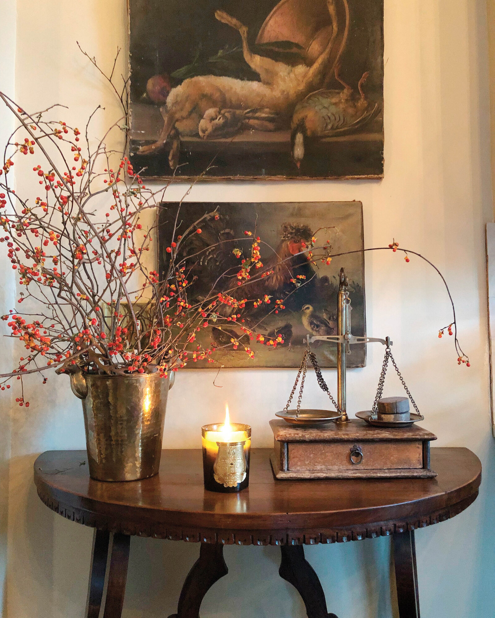 small table with artwork above and tall flowers