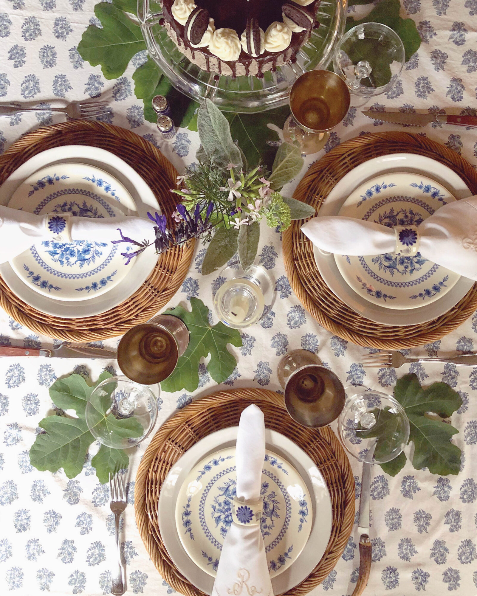 table setting of printed linens and wicker chargers with surrounding greenery