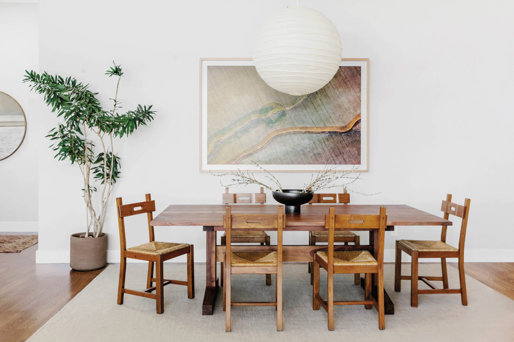 table with artwork and big globe pendant hanging above