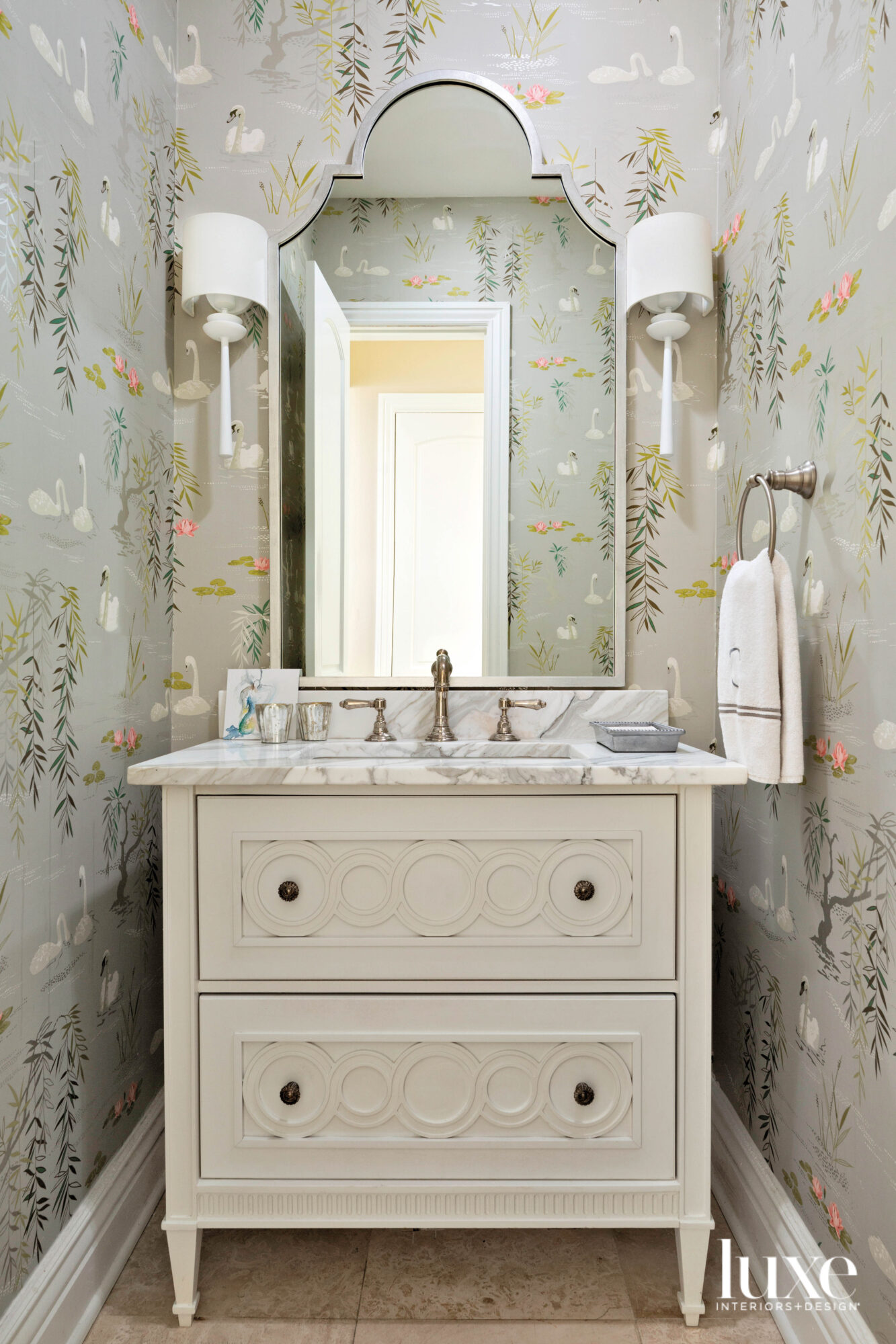 Powder bathroom with swan-patterned wallpaper...